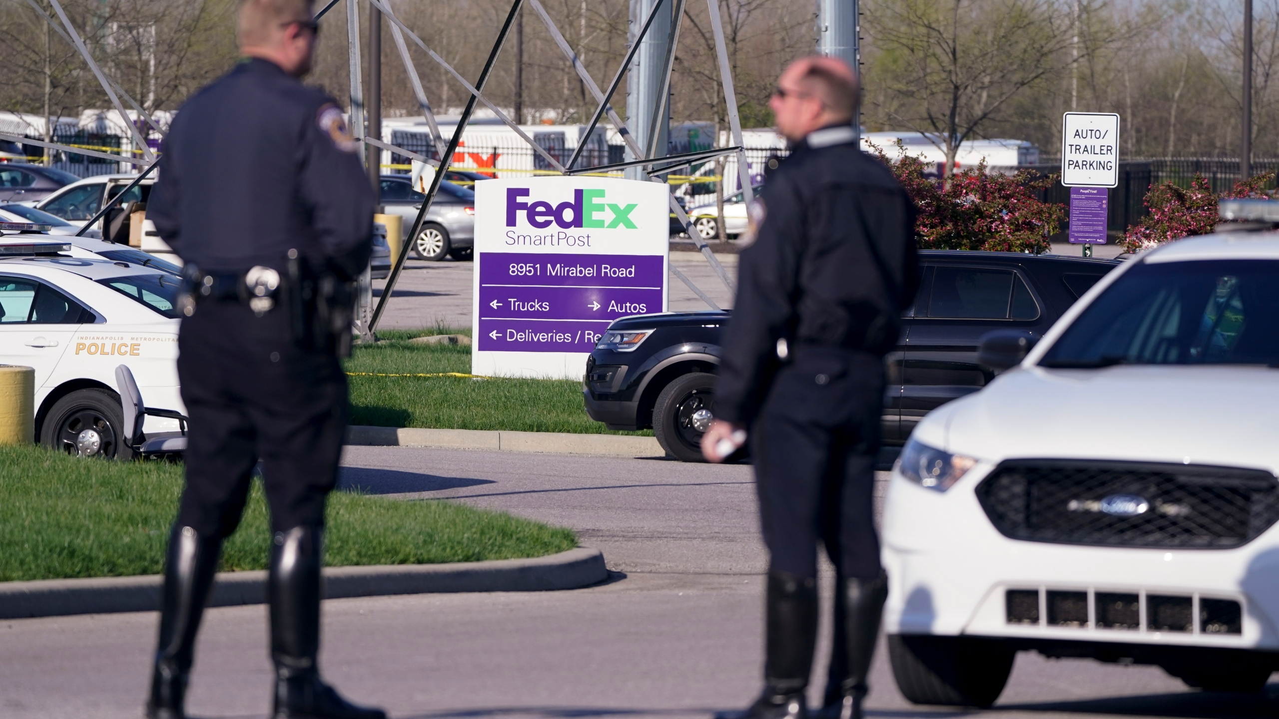 Police stand near the scene where multiple people were shot at the FedEx Ground facility early Friday morning, April 16, 2021, in Indianapolis. (AP Photo/Michael Conroy)