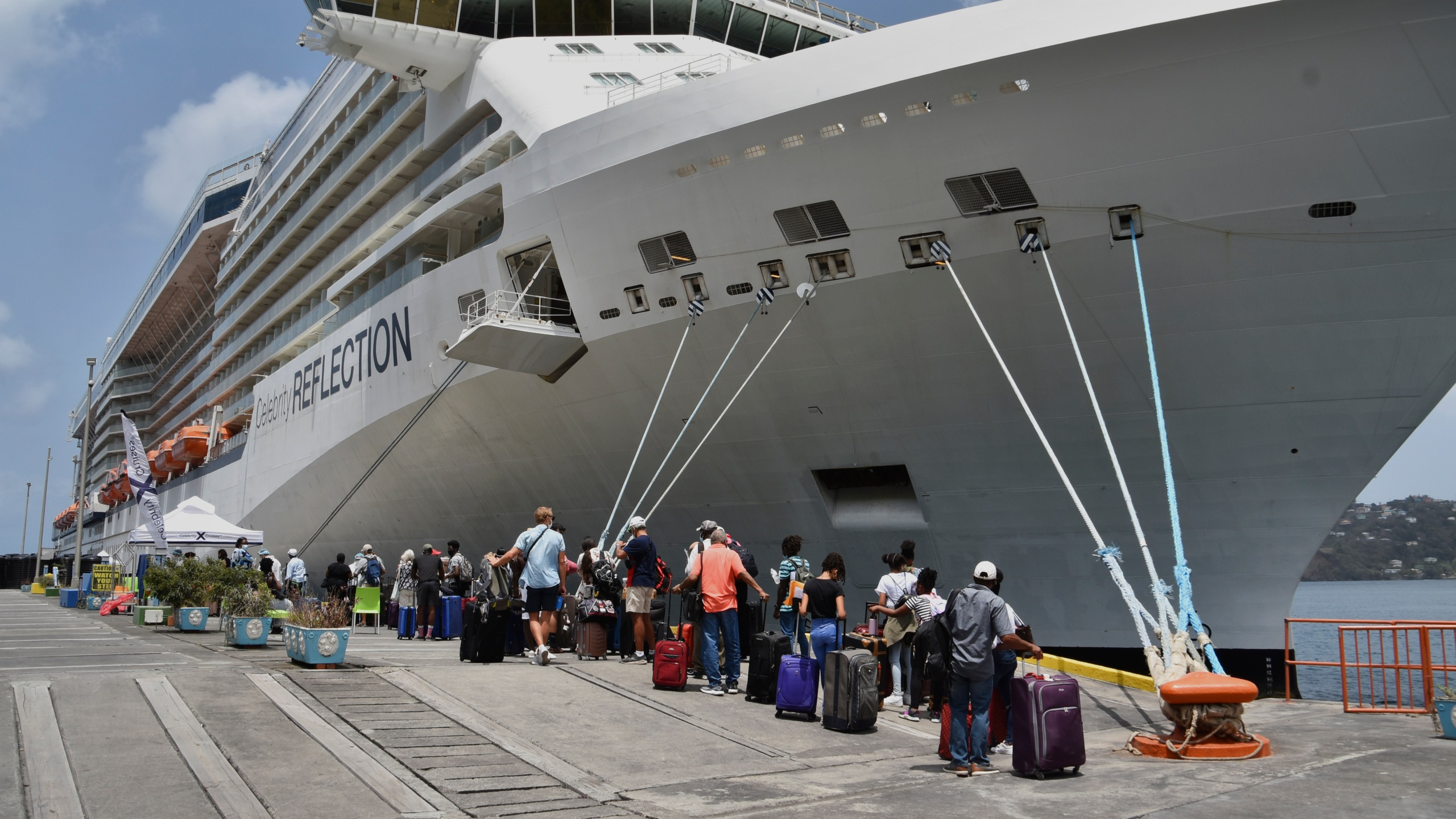 British, Canadian and U.S. nationals line up alongside the Royal Caribbean cruise ship Reflection to be evacuated free of charge, in Kingstown on the eastern Caribbean island of St. Vincent, Friday, April 16, 2021. La Soufriere volcano has shot out another explosive burst of gas and ash Friday morning as the cruise ship arrived to evacuate some of the foreigners who had been stuck on a St. Vincent island by a week of violent eruptions. (AP Photo/Orvil Samuel)