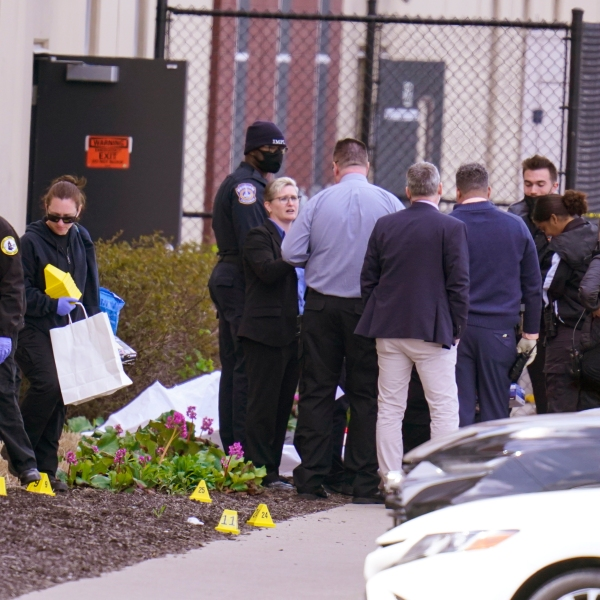Authorities confer at the scene where multiple people were shot at the FedEx Ground facility early Friday morning, April 16, 2021, in Indianapolis. A gunman killed several people and wounded others before taking his own life in a late-night attack at a FedEx facility near the Indianapolis airport, police said. (AP Photo/Michael Conroy)