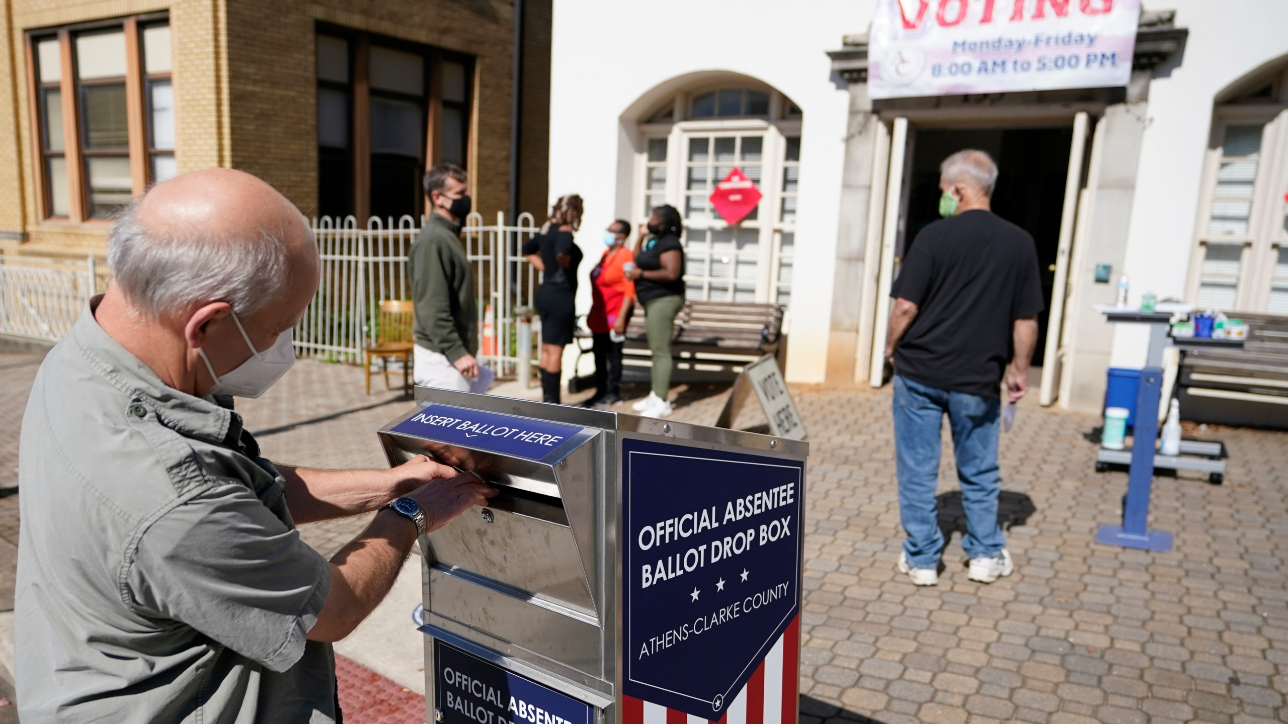 In this Monday, Oct. 19, 2020 file photo, a voter submits a ballot in an official drop box during early voting in Athens, Ga. Ballot drop boxes were enormously popular during the 2020 election, with few problems reported. Yet they have drawn the attention of Republican lawmakers in key states who say security concerns warrant new restrictions. (AP Photo/John Bazemore, File)