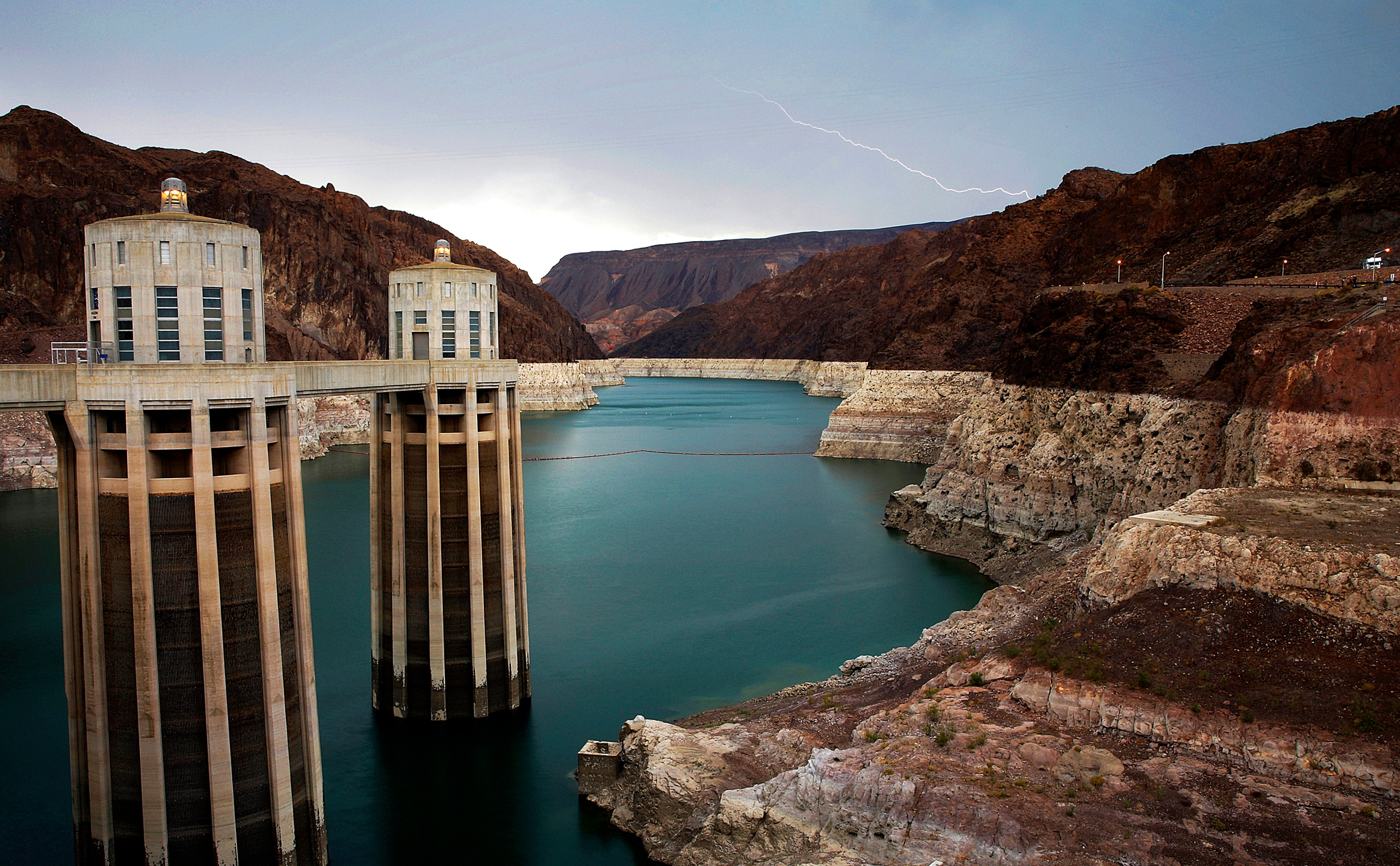 In this July 28, 2014, file photo, lightning strikes over Lake Mead near Hoover Dam that impounds Colorado River water at the Lake Mead National Recreation Area in Arizona. The Bureau of Reclamation is forecasting first-ever water shortages because of falling levels at Lake Mead and says the reservoir could drop so low that it might not be able to generate electricity at Hoover Dam. (AP Photo/John Locher, File)