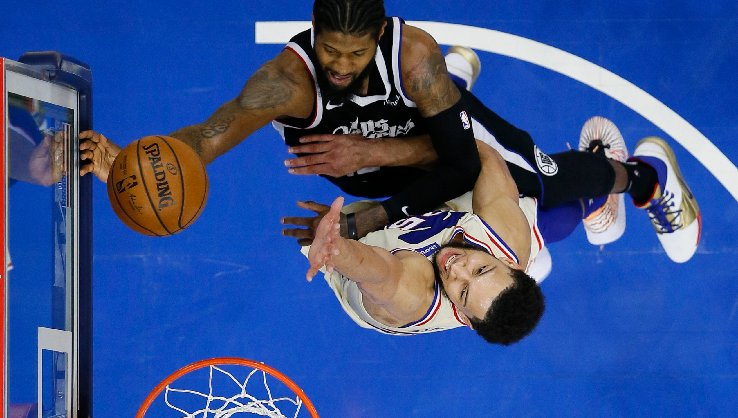Los Angeles Clippers' Paul George, top, goes up for a shot against Philadelphia 76ers' Ben Simmons during the second half of an NBA basketball game in Philadelphia April 16, 2021. (Matt Slocum / Associated Press)