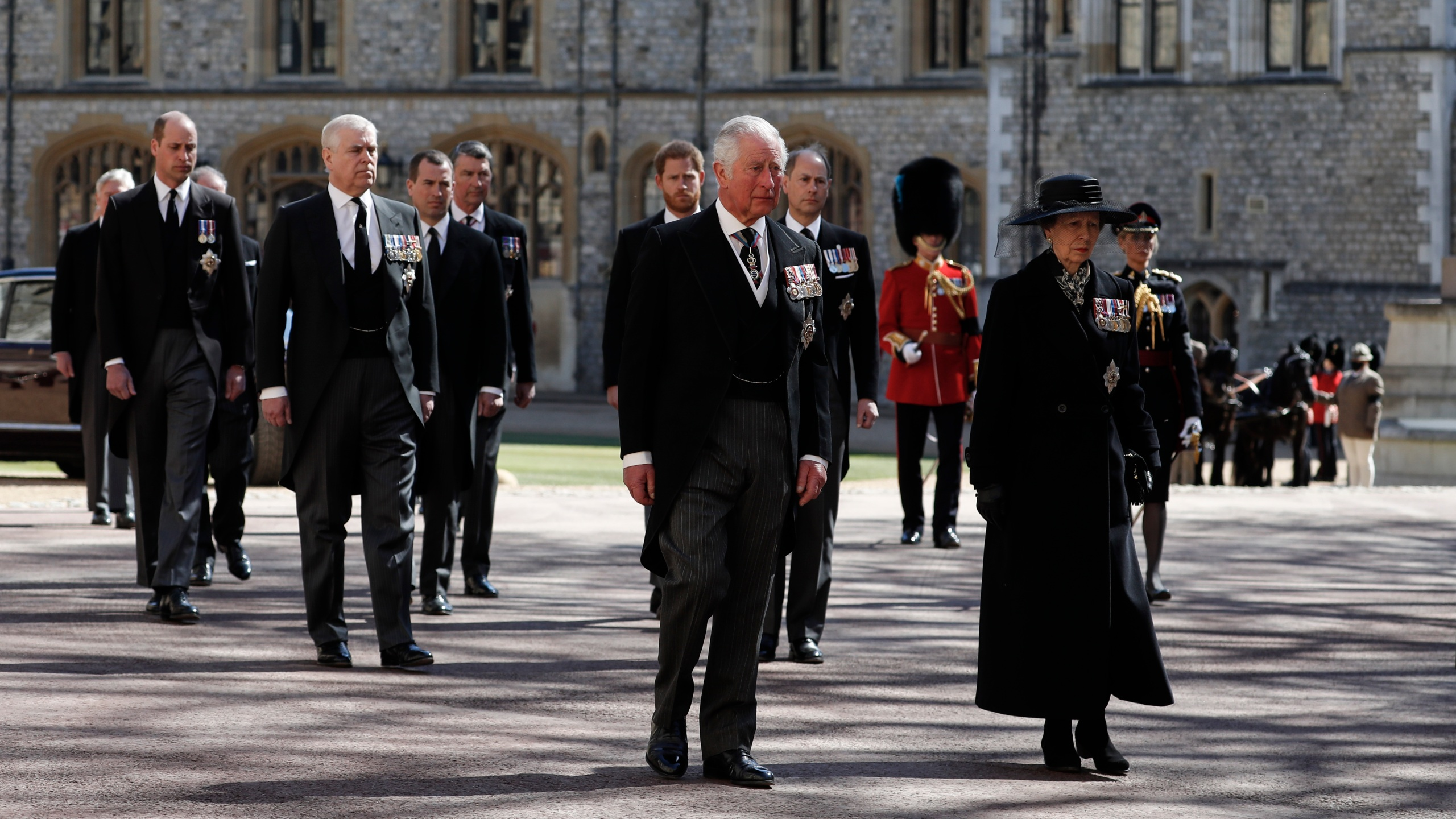 From front left, Britain's Prince Charles, Princess Anne, Prince Andrew. Prince Edward, Prince William, Peter Phillips, Prince Harry, Earl of Snowdon and Tim Laurence follow the coffin in a ceremonial procession for the funeral of Britain's Prince Philip inside Windsor Castle in Windsor, England Saturday April 17, 2021. Prince Philip died April 9 at the age of 99 after 73 years of marriage to Britain's Queen Elizabeth II. (Alastair Grant/Pool via AP)