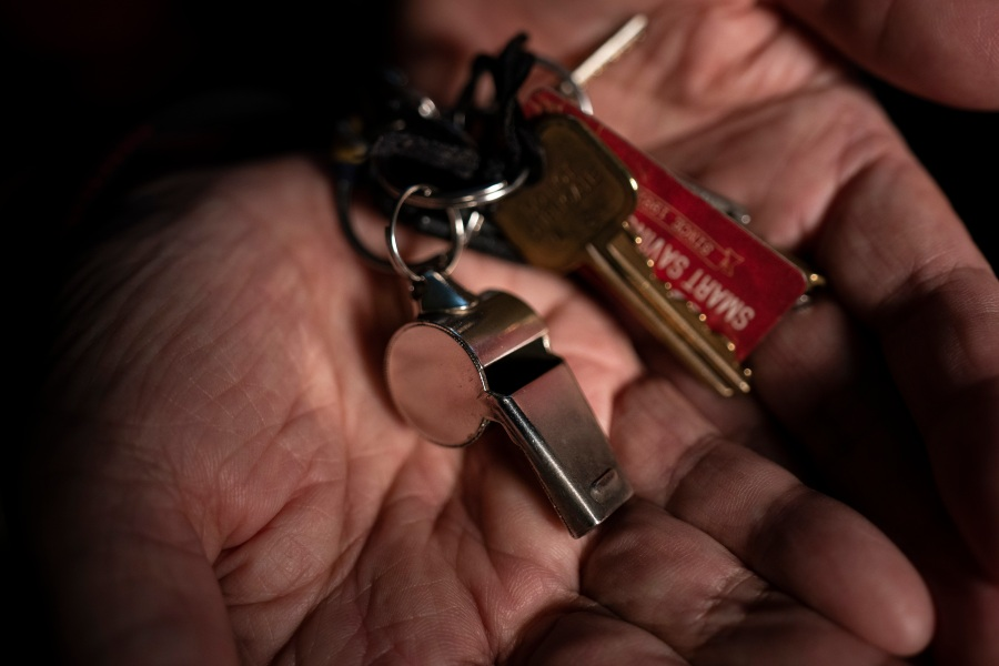 Yong Sin Kim, an 85-year-old South Korean immigrant, shows a whistle attached to his keychain while pausing for photos in his apartment in downtown Los Angeles on March 25, 2021. (Jae C. Hong / Associated Press)