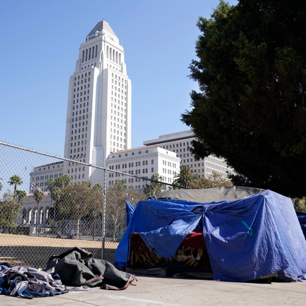 A homeless person's tent stands just outside Grand Park with Los Angeles City Hall in the background on Oct. 28, 2020. (Chris Pizzello / Associated Press)