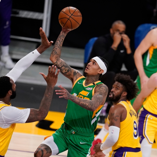 Utah Jazz guard Jordan Clarkson, center, shoots over Los Angeles Lakers center Andre Drummond, left, during the first half of an NBA basketball game in Los Angeles on April 19, 2021. (Marcio Jose Sanchez / Associated Press)