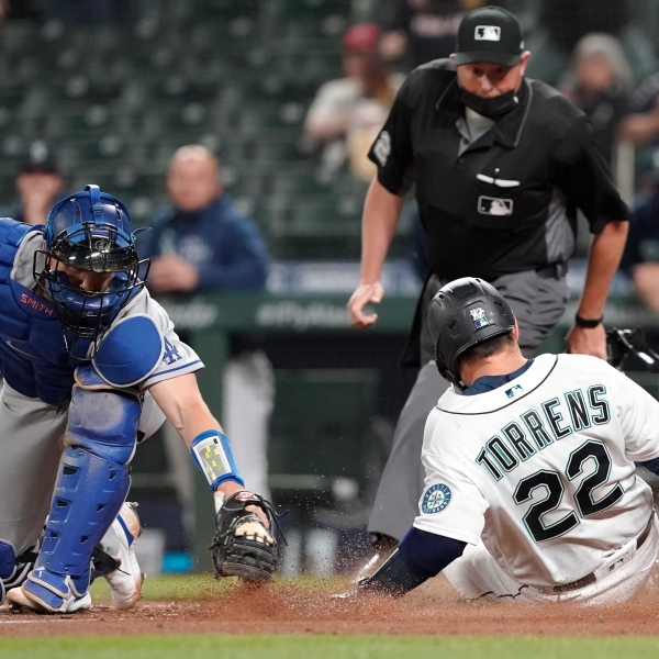Seattle Mariners' Luis Torrens slides safely home as Los Angeles Dodgers catcher Will Smith attempts the tag during the fourth inning of a baseball game in Seattle on April 19, 2021. (Ted S. Warren / Associated Press)