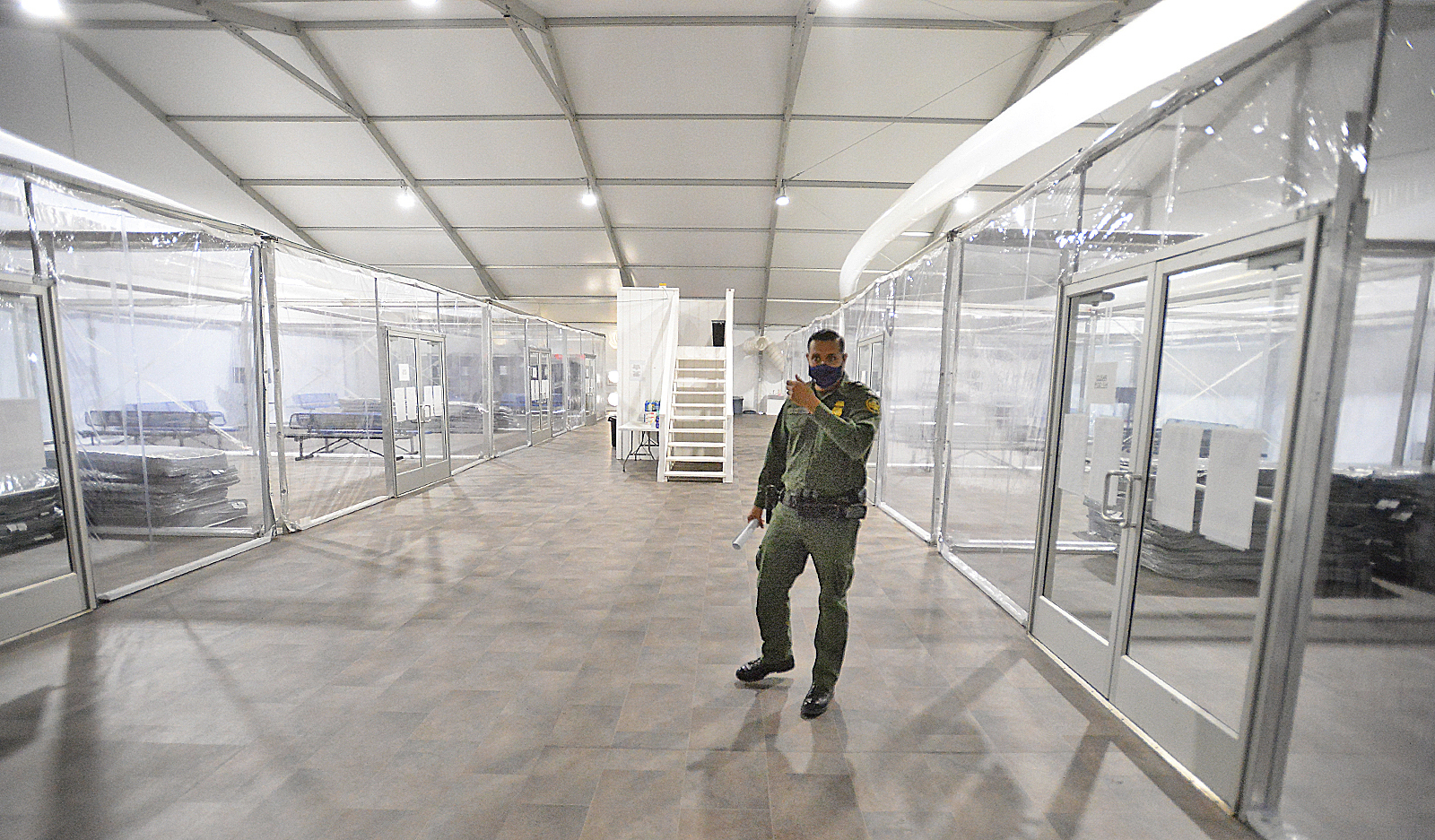 U.S. Border Patrol Agent Fidel Cabrera leads a tour of one of four living areas inside a processing facility in Yuma during an open house on April 20, 2021. (Randy Hoeft / The Yuma Sun via Associated Press)
