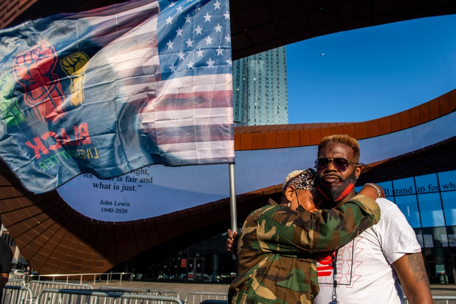 Ingrid Noel, 51, left, weeps on the shoulder of Robert Bolden, at a rally outside the Barclays Center in Brooklyn on April 20, 2021. Former Minneapolis police Officer Derek Chauvin has been convicted of murder and manslaughter in the death of George Floyd. (Brittainy Newman / Associated Press)