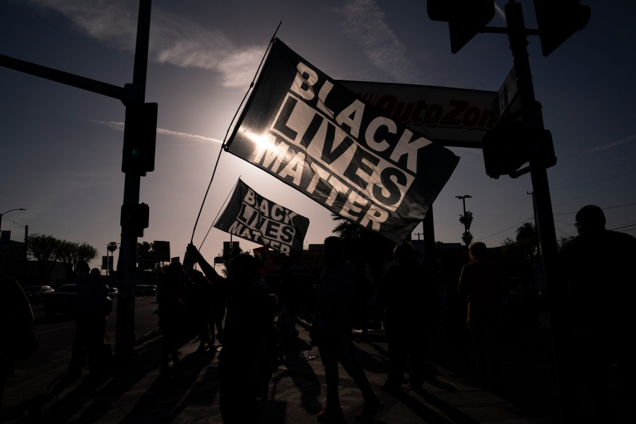 People hold Black Lives Matter flags at the intersection of Florence and Normandie avenues, on April 20, 2021, in Los Angeles, after a guilty verdict was announced at the trial of former Minneapolis police Officer Derek Chauvin for the 2020 death of George Floyd. (AP Photo/Jae C. Hong)