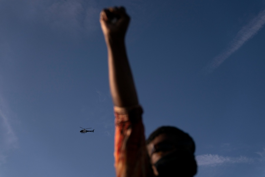 A Los Angeles Police helicopter hovers as Joyce Robertson, foreground, clenches her fist at the intersection of Florence and Normandie Avenues, on April 20, 2021, in Los Angeles, after a guilty verdict was announced at the trial of former Minneapolis police Officer Derek Chauvin for the 2020 death of George Floyd. (AP Photo/Jae C. Hong)