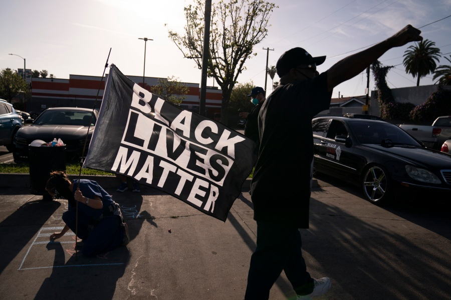 A person with a Black Lives Matter flag writes a message on a sidewalk at the intersection of Florence and Normandie Avenues in Los Angeles, on April 20, 2021, after a guilty verdict was announced at the trial of former Minneapolis police Officer Derek Chauvin for the 2020 death of George Floyd. (AP Photo/Jae C. Hong)