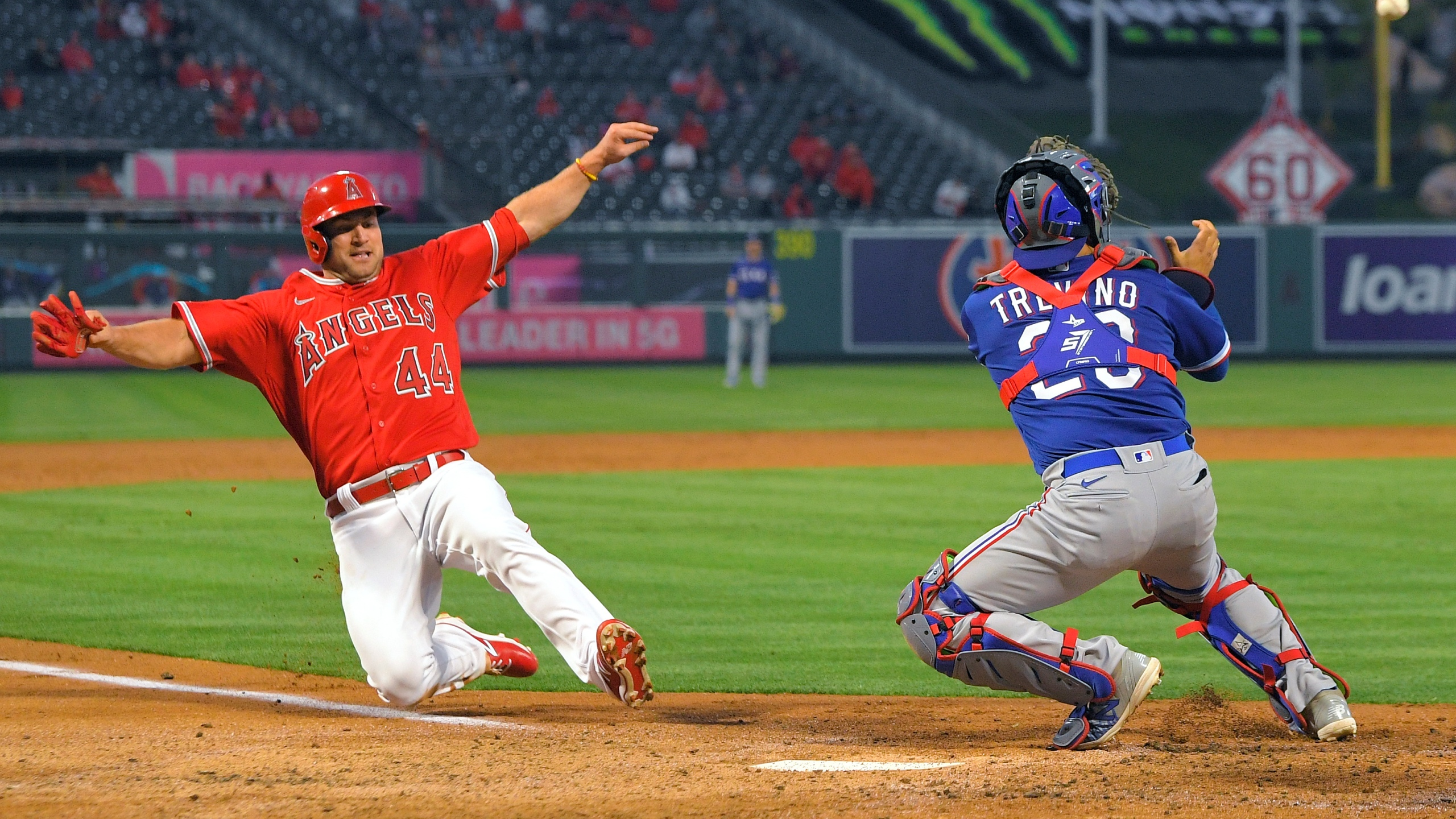 Los Angeles Angels' Scott Schebler, left, scores on a sacrifice fly hit by David Fletcher as Texas Rangers catcher Jose Trevino takes a late throw during the third inning of a baseball game in Anaheim on April 20, 2021. (Mark J. Terrill / Associated Press)