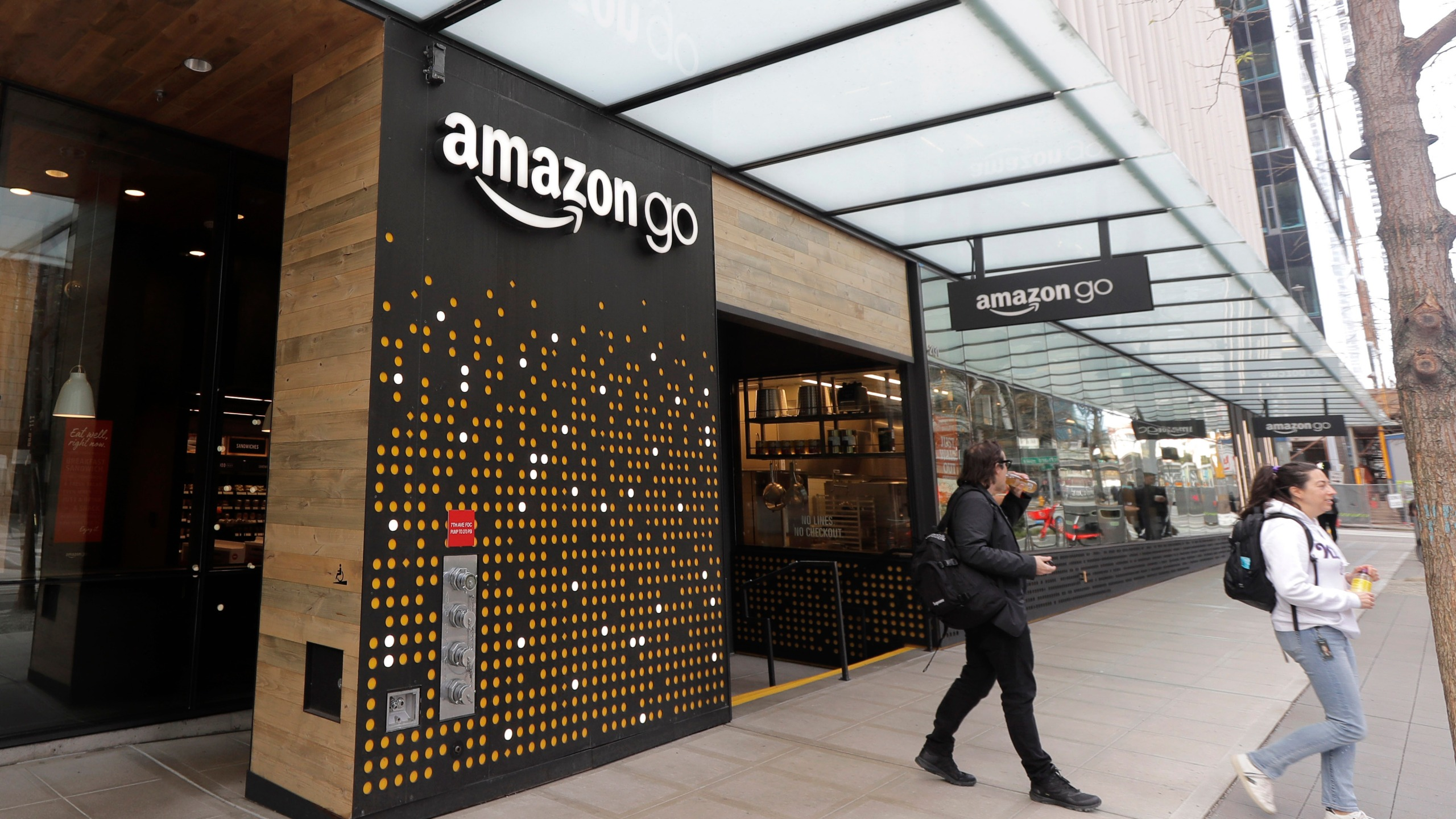 In this March 4, 2020 file photo, people walk out of an Amazon Go store, in Seattle. Amazon said Wednesday, April 21, 2021 that it is rolling out its pay-by-palm technology to some of its Whole Foods supermarkets. The technology, called Amazon One, lets shoppers scan the palm of their hand and connect it to their credit card or Amazon accounts. (AP Photo/Ted S. Warren, File)