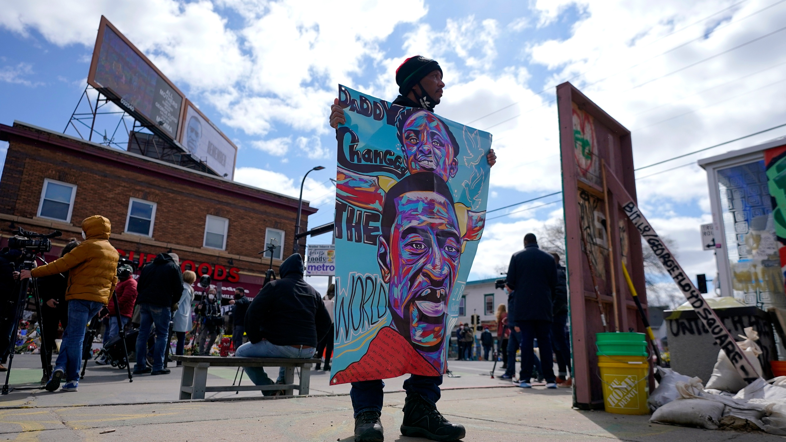 A man holds a sign at George Floyd Square, Wednesday, April 21, 2021, in Minneapolis, a day after former Minneapolis police Officer Derek Chauvin was convicted on all counts for the 2020 death of Floyd. (AP Photo/Julio Cortez)
