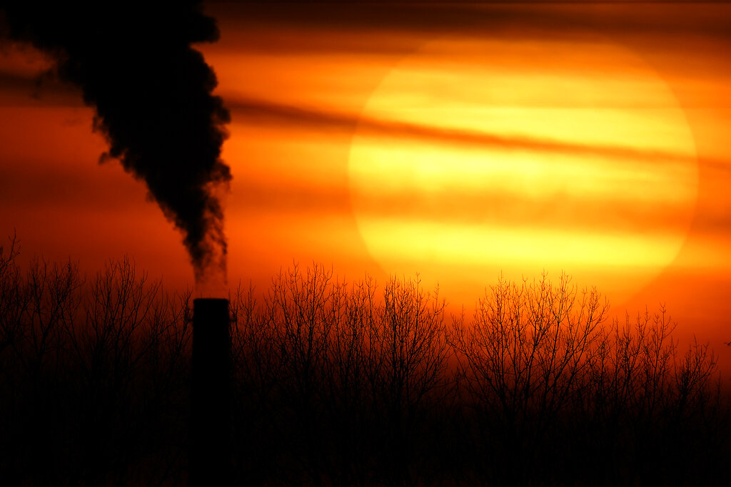 In this Feb. 1, 2021 file photo, emissions from a coal-fired power plant are silhouetted against the setting sun in Independence, Mo. President Joe Biden is convening a coalition of the willing, the unwilling, the desperate-for-help and the avid-for-money for a two-day summit aimed at rallying the world's worst polluters to do more to slow climate change. (AP Photo/Charlie Riedel, File)
