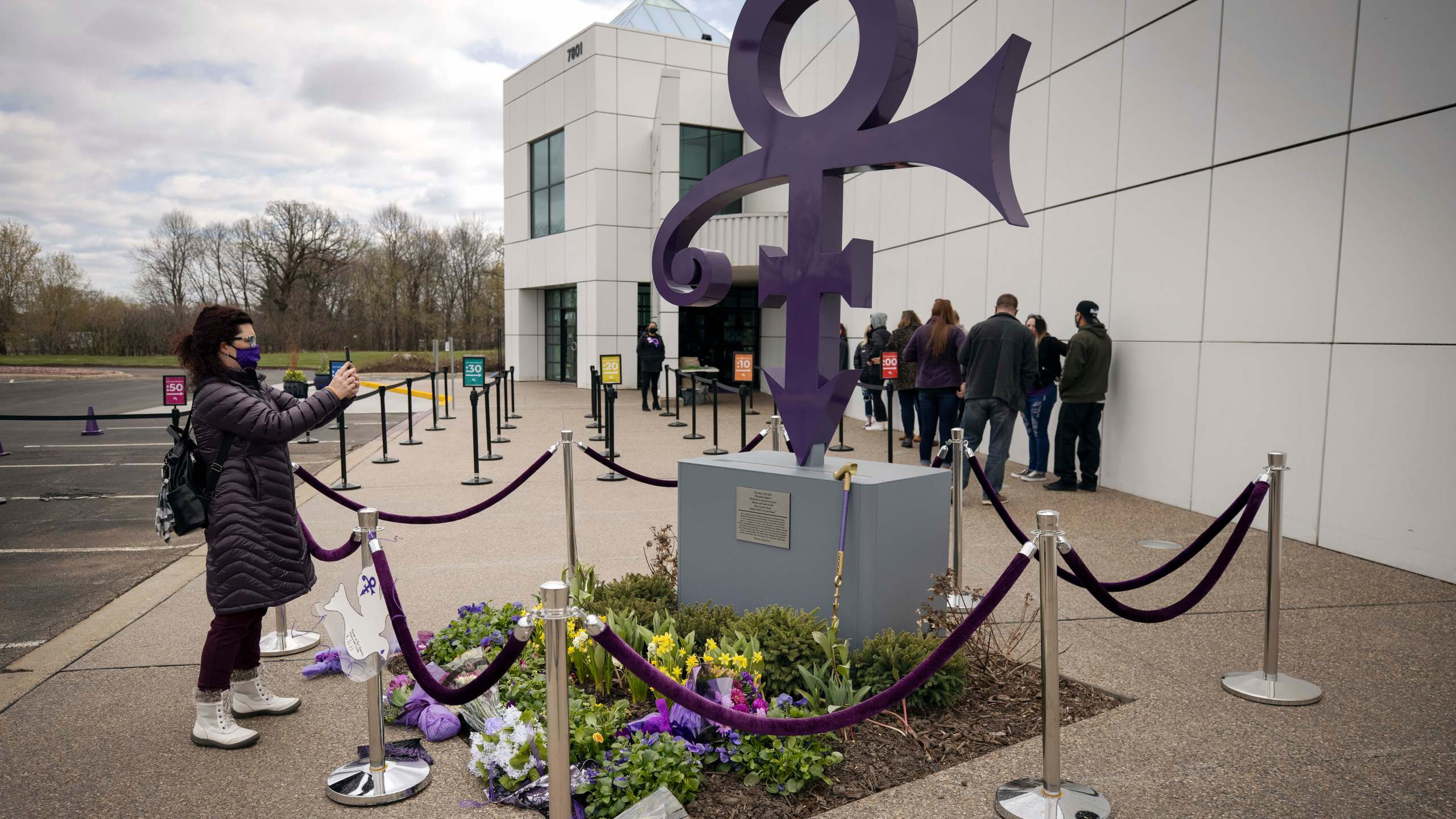 A fan takes a photo of a memorial on April 21, 2021 as others line up to go into Paisley Park in Chanhassen, Minn., on the fifth anniversary of Prince's death. (Stacy Bengs/Associated Press)