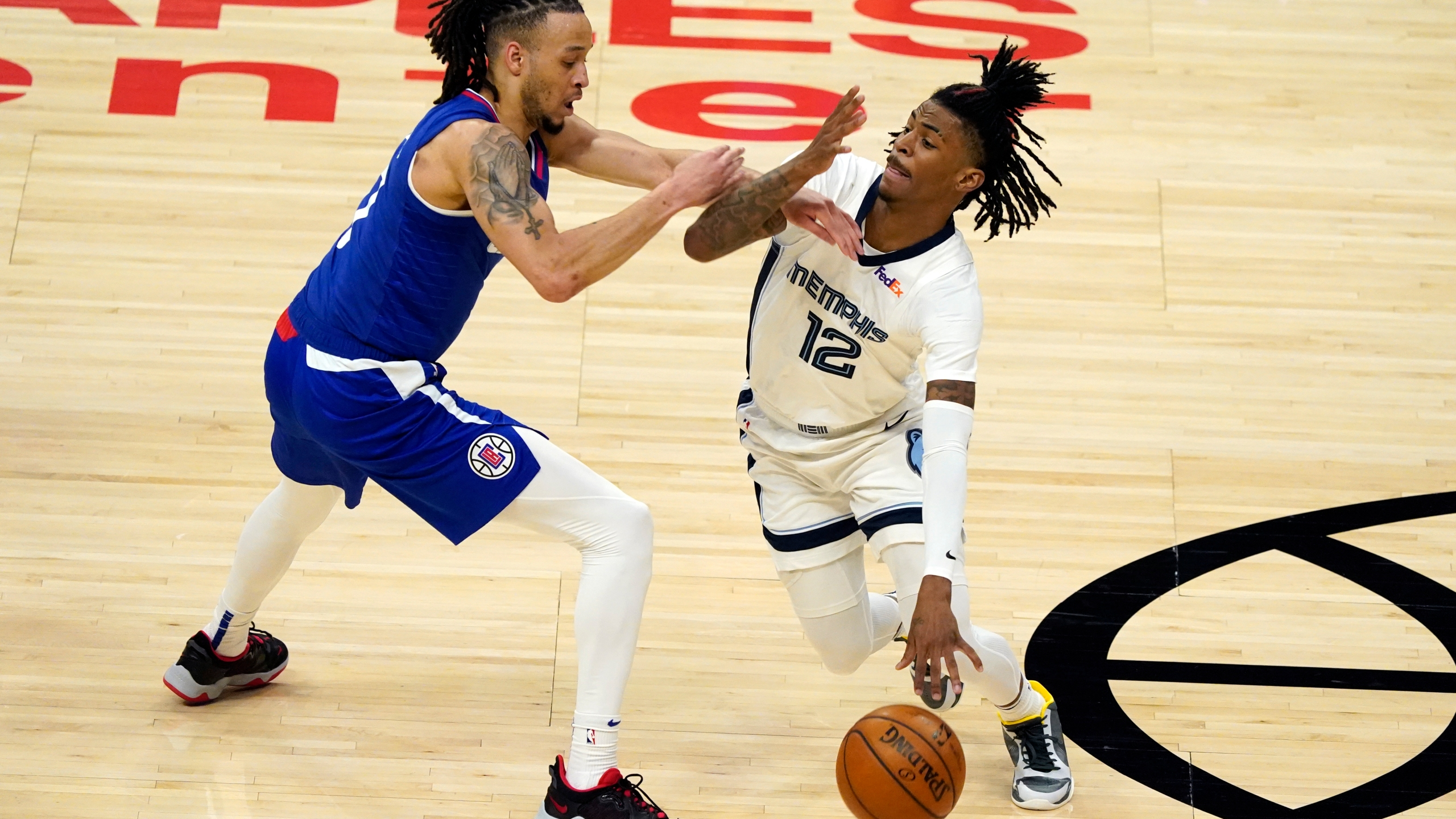 Memphis Grizzlies guard Ja Morant (12) is defended by Los Angeles Clippers guard Amir Coffey during the first half of an NBA basketball game in Los Angeles on April 21, 2021. (Marcio Jose Sanchez / Associated Press)
