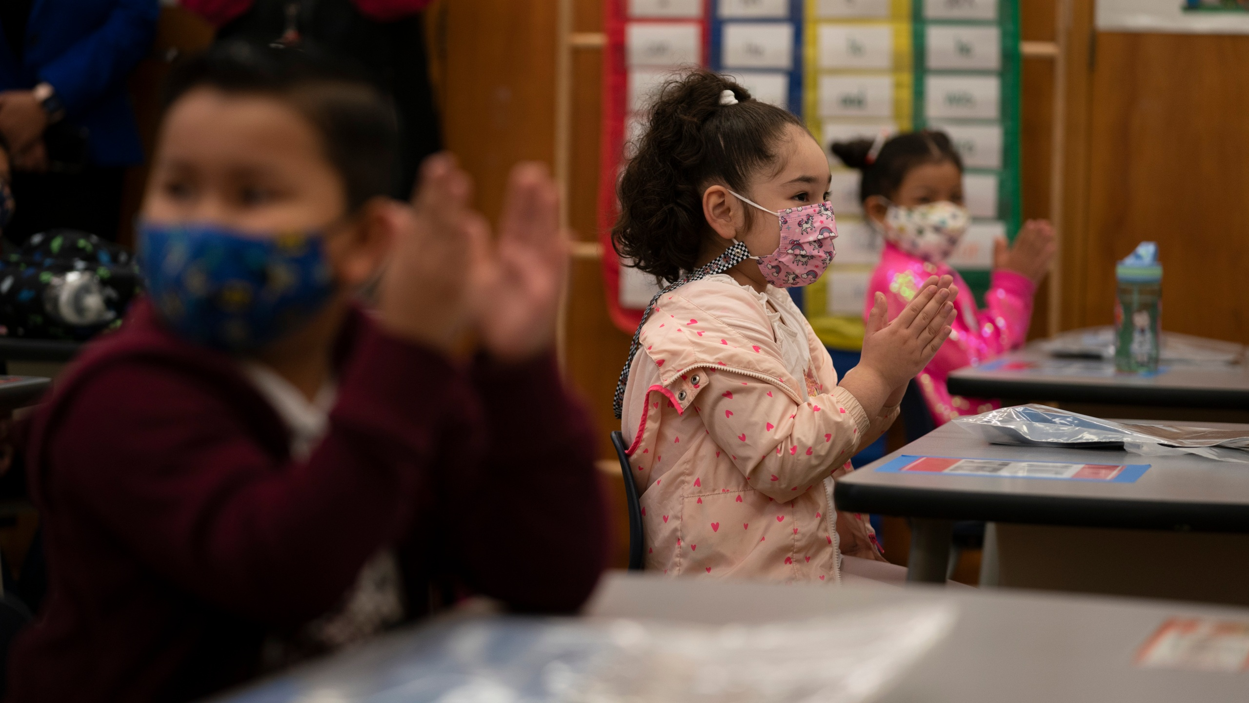 First graders applaud while listening to their teacher in a classroom on the first day of in-person learning at Heliotrope Avenue Elementary School in Maywood on April 13, 2021. (Jae C. Hong / Associated Press)