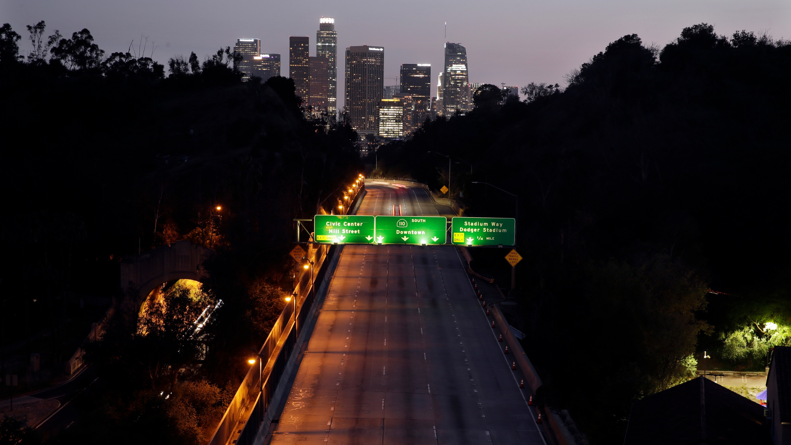 In this April 2, 2020, file photo, light traffic is seen on the 110 freeway with the city skyline in the background in Los Angeles. (AP Photo/Marcio Jose Sanchez, File)
