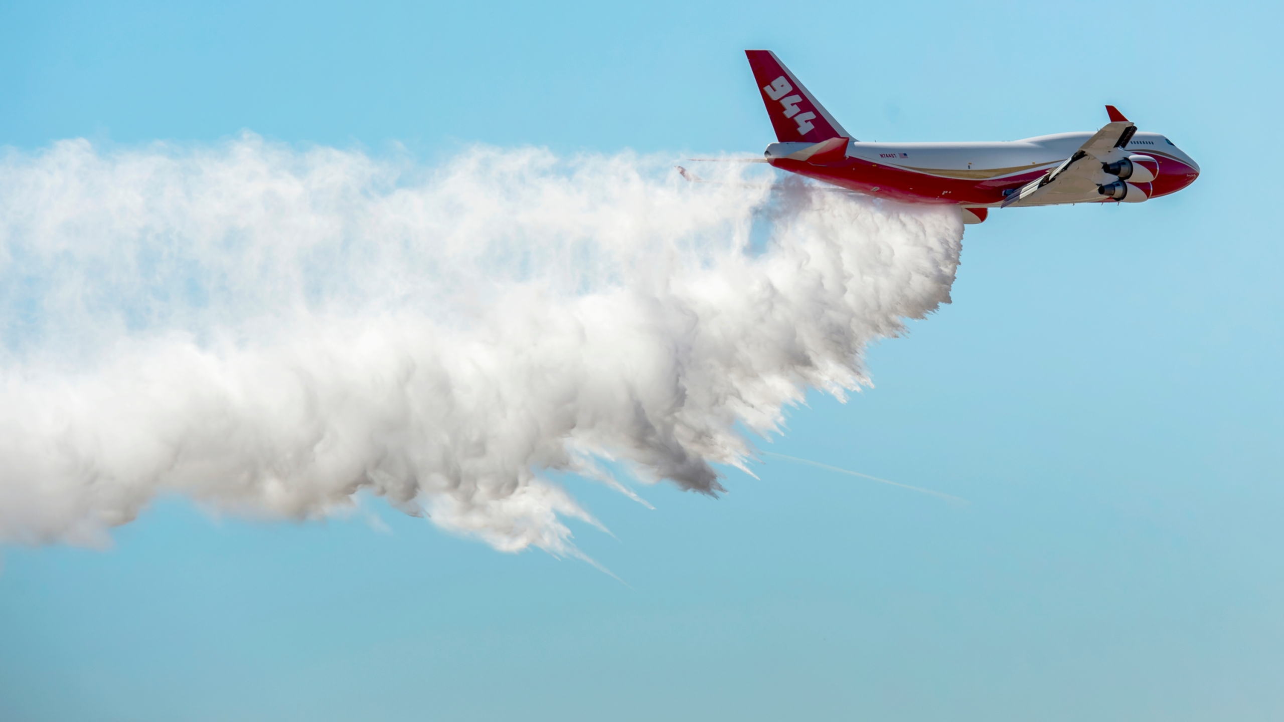 A Boeing 747-400 Global SuperTanker drops half a load of its 19,400-gallon capacity during a ceremony at Colorado Springs, Colo., on May 5, 2016. (Christian Murdock / The Gazette via Associated Press)