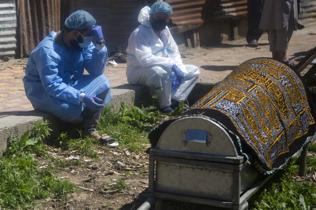 Relatives mourn near a coffin containing the body of a person who died of COVID-19 in Srinagar, Indian controlled Kashmir, on April 25, 2021. (AP Photo/Mukhtar Khan)