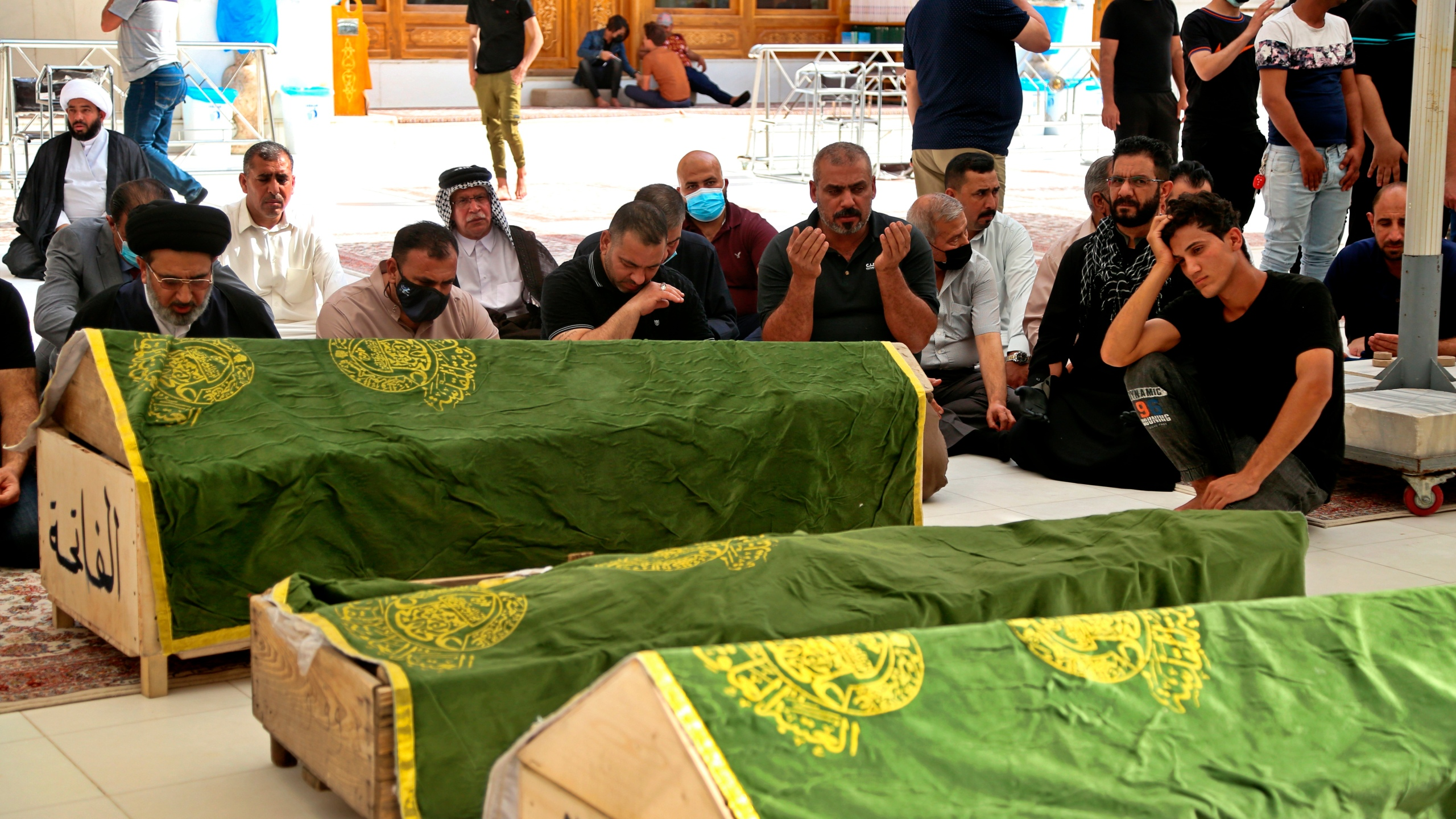 Mourners pray near the coffins of coronavirus patients who were killed in a hospital fire in Iraq, April 25, 2021. (AP Photo/Anmar Khalil)