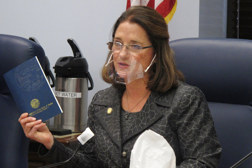 In this Jan. 27, 2021 file photo, Alaska state Sen. Lora Reinbold, an Eagle River Republican, holds a copy of the Alaska Constitution during a committee hearing in Juneau, Alaska. (AP Photo/Becky Bohrer, File)