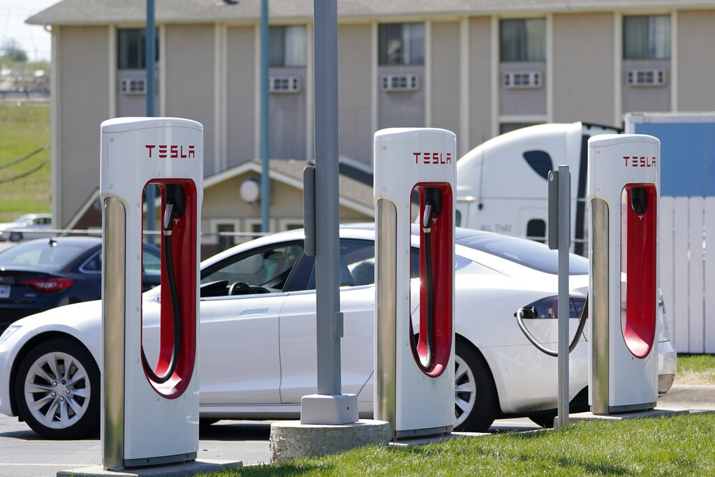 In this Monday, April 5, 2021 file photo, a Tesla electric vehicle charges at a station in Topeka, Kan. (AP Photo/Orlin Wagner)
