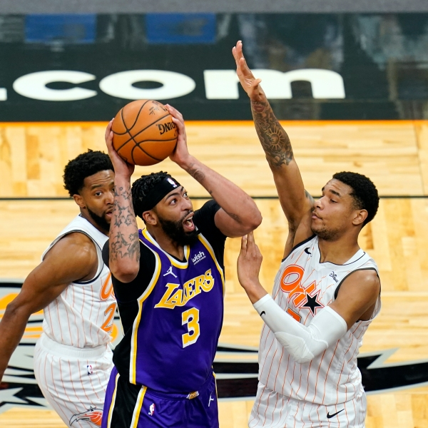 Los Angeles Lakers forward Anthony Davis takes shot as he gets between Orlando Magic guard Chasson Randle, left, and forward Chuma Okeke during the first half of an NBA basketball game in Orlando, Fla., on April 26, 2021. (John Raoux / Associated Press)