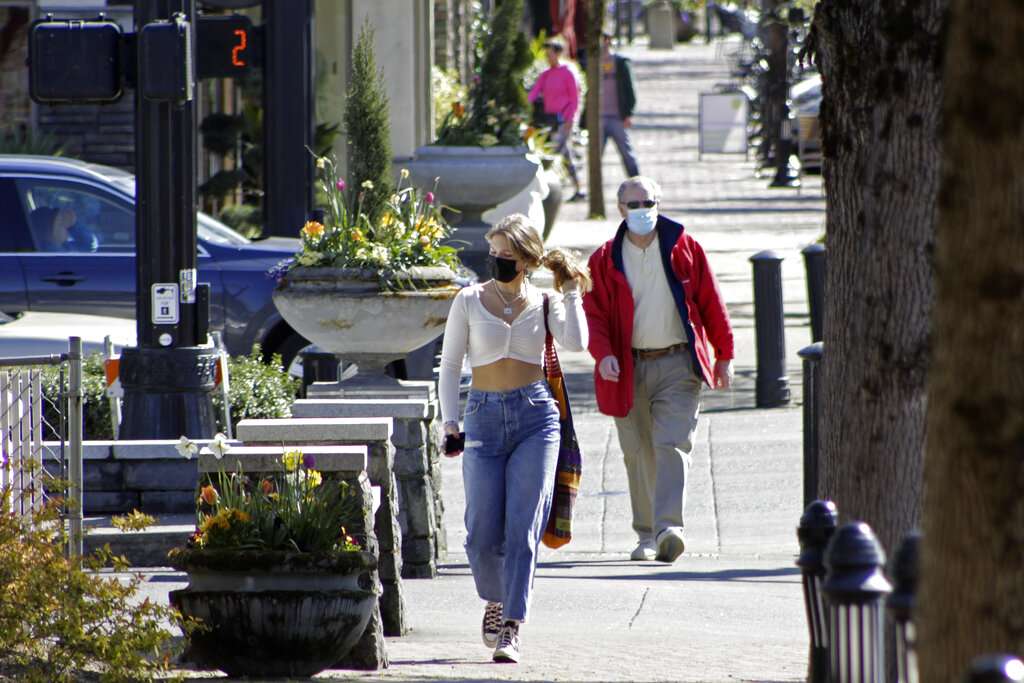 In this April 11, 2021, file photo, residents wearing masks walk in downtown Lake Oswego, Oregon. (AP Photo/Gillian Flaccus, File)