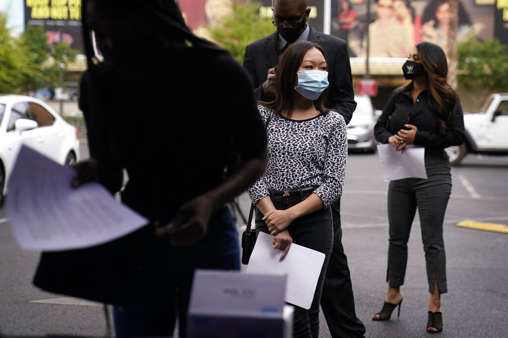 People wait in line, resumes in hand, while waiting to apply for jobs during an outdoor hiring event for the Circa resort and casino, Tuesday, April 27, 2021, in Las Vegas. (AP Photo/John Locher)