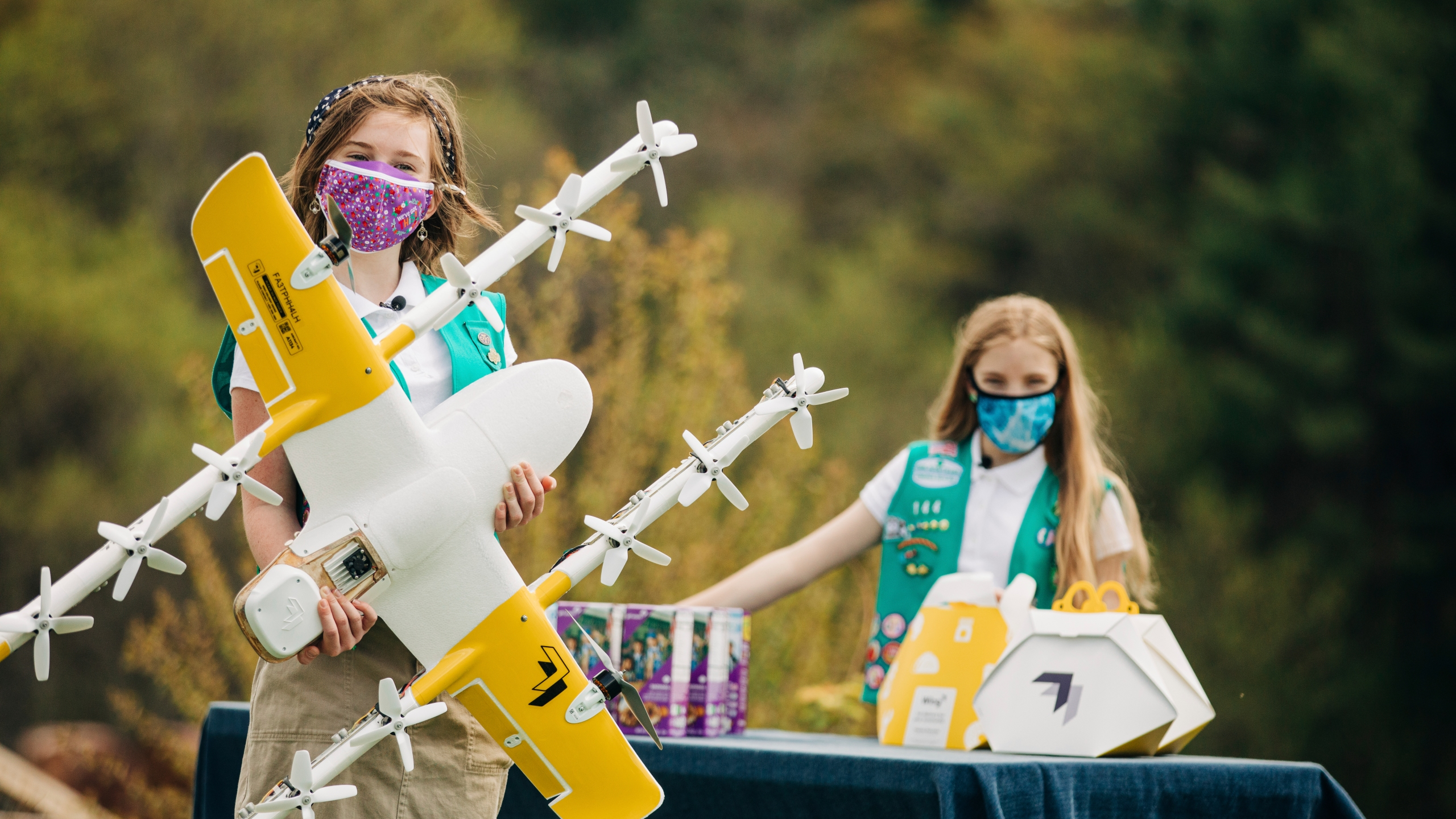 In this April 14, 2021 image provided by Wing LLC., Girl Scouts Alice Goerlich, right, and Gracie Walker pose with a Wing delivery drone in Christiansburg, Va. The company is testing drone delivery of Girl Scout cookies in the area. (Sam Dean/ Wing LLC via AP)