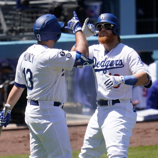Los Angeles Dodgers' Justin Turner, right, celebrates his solo home run with Max Muncy during the third inning of a baseball game against the Cincinnati Reds in Los Angeles on April 28, 2021. (Marcio Jose Sanchez / Associated Press)