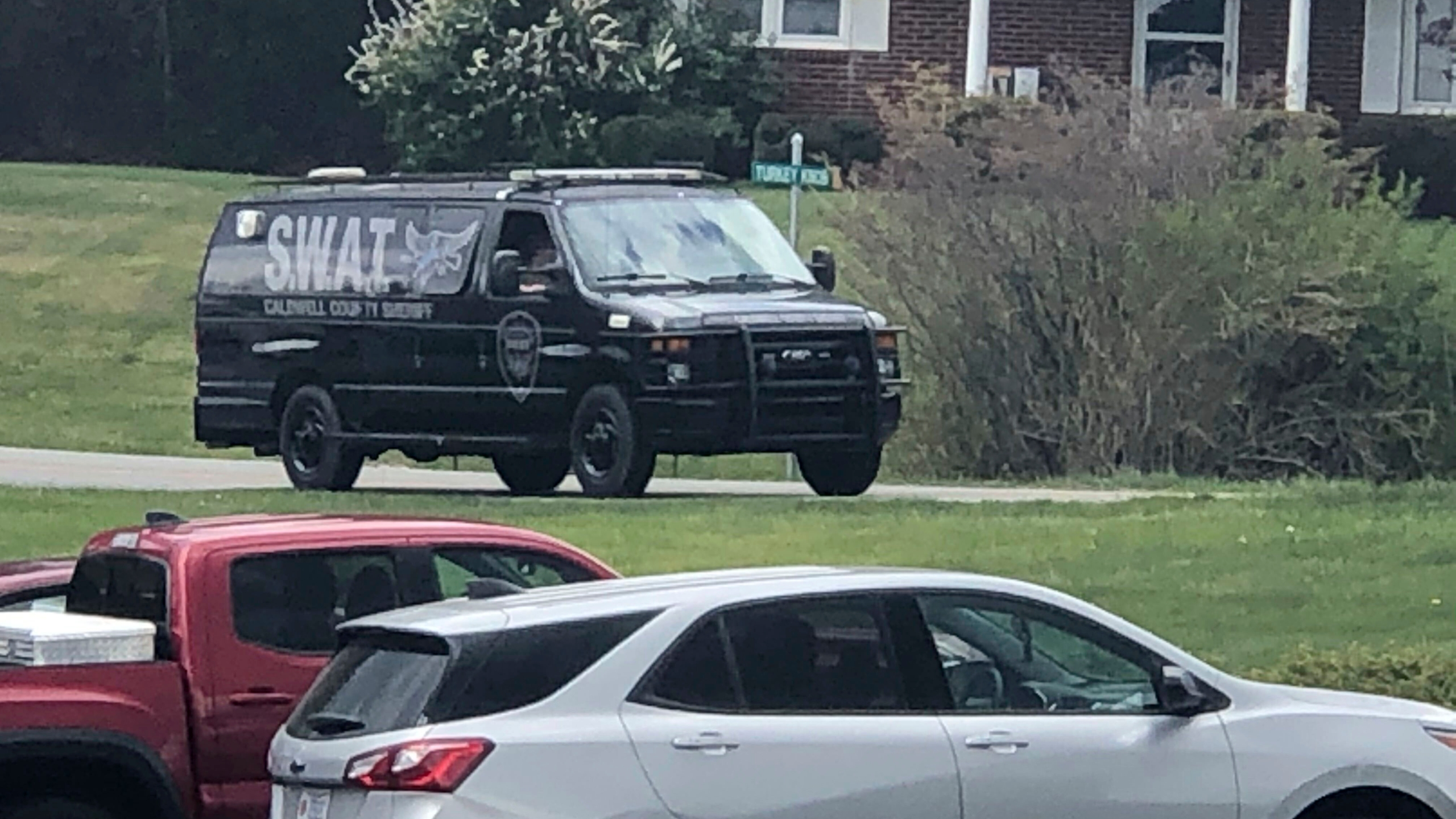 In this photo provided by WJZY, a tactical van from Caldwell County, North Carolina, sits on stand-by at a staging area in Boone, N.C., on Wednesday, April 28, 2021. Law enforcement agencies responded to a standoff in Boone in which two Watauga County sheriff's deputies were shot and wounded. (Morgan Frances/WJZY via AP)