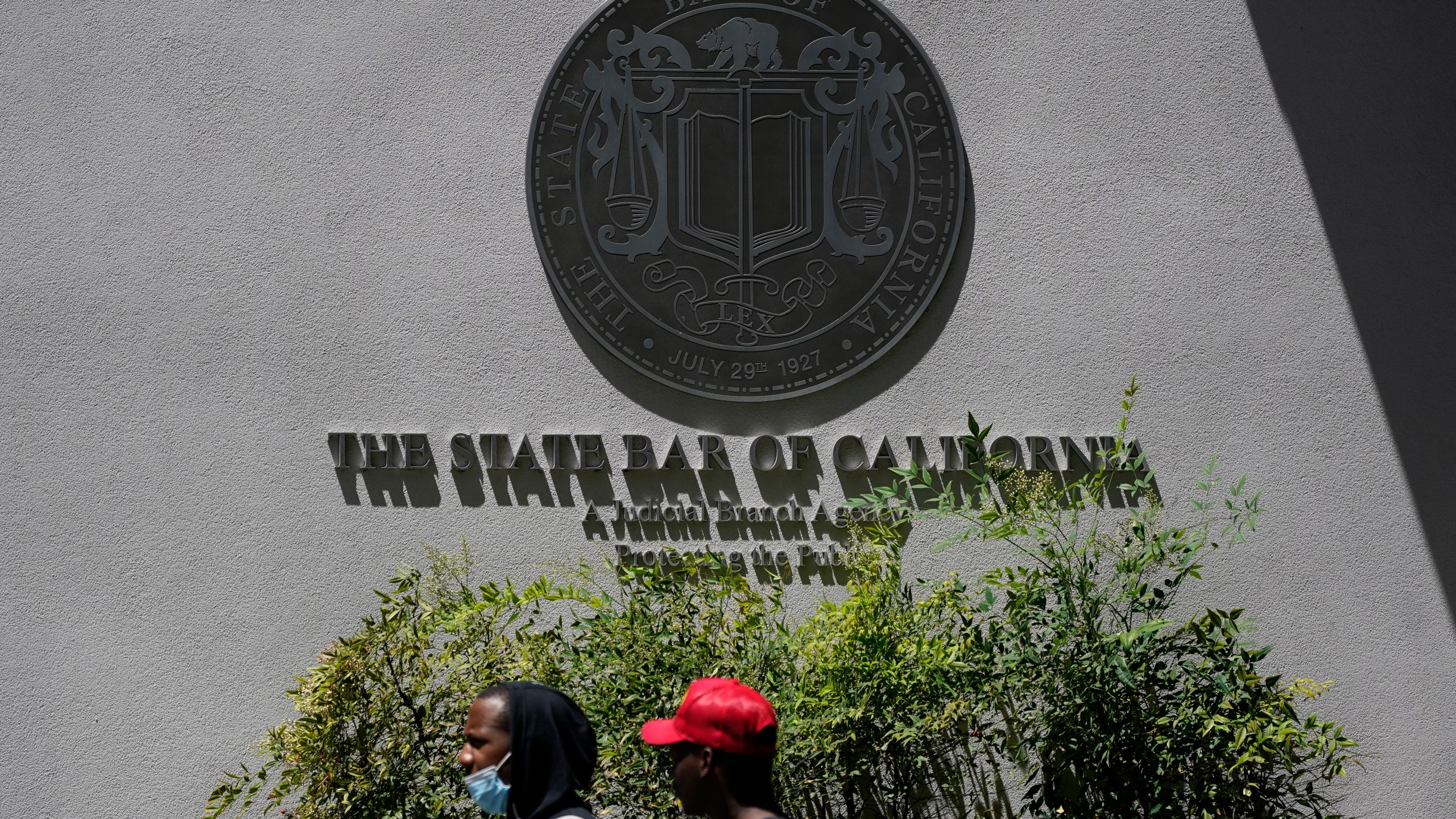 People walk past the entrance of The State Bar of California office Thursday, April 29, 2021, in Los Angeles. (AP Photo/Ashley Landis)