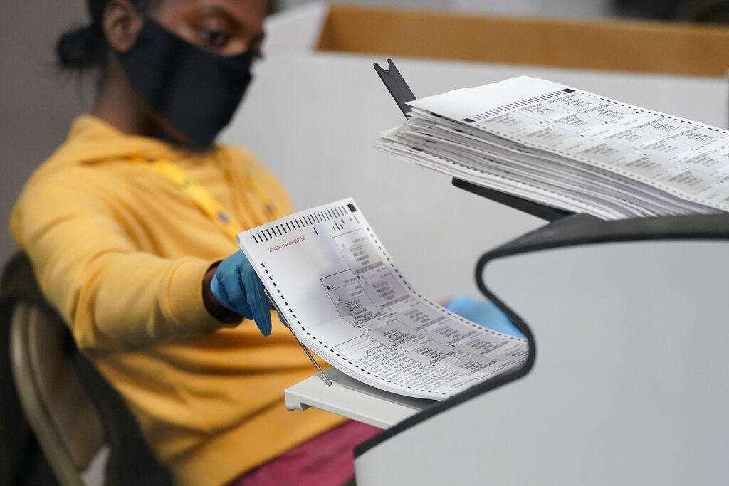 In this Nov. 5, 2020, file photo, a county election worker scans mail-in ballots at a tabulating area at the Clark County Election Department in Las Vegas. (AP Photo/John Locher, File)