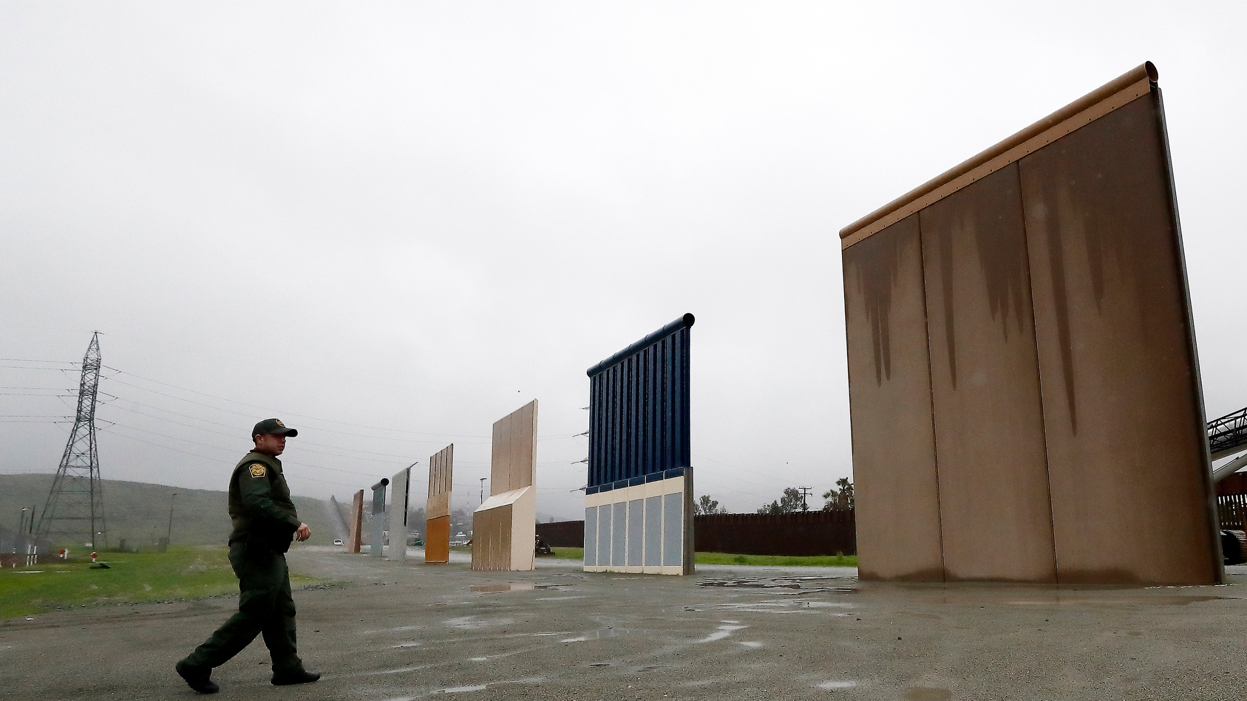 In this Feb. 5, 2019 file photo, U.S. Border Patrol agent Vincent Pirro walks towards prototypes for a border wall in San Diego. The Biden administration says it will begin work to address flooding and soil erosion risks from unfinished walls on the U.S. border with Mexico. It also began providing answers on how it will use unspent money from shutting down one of President Donald Trump's signature domestic projects. The Defense Department says it will use unobligated money for military construction projects for its initial purpose. (AP Photo/Gregory Bull, File)