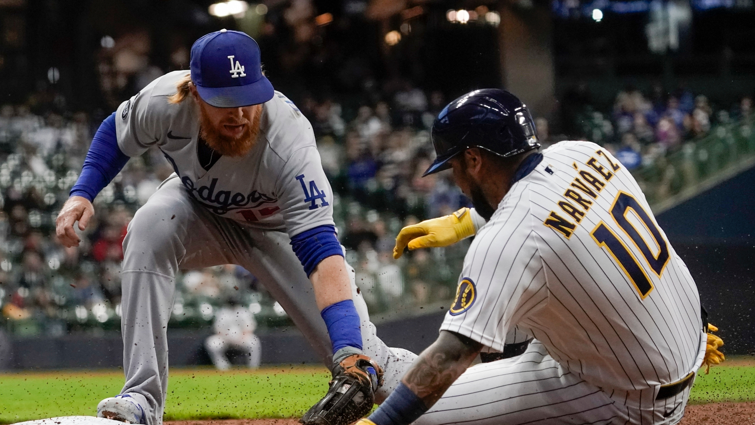 Los Angeles Dodgers' Justin Turner tags out Milwaukee Brewers' Omar Narvaez at first during the first inning of a baseball game Friday, April 30, 2021, in Milwaukee. (AP Photo/Morry Gash)