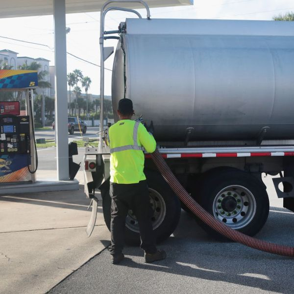 A tanker truck driver resupplies a gas station with fuel in this file photo. (Scott Olson/Getty Images)