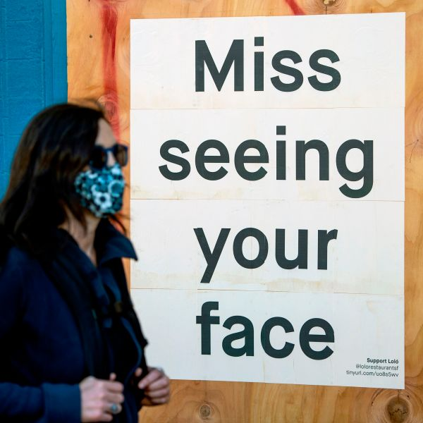 A woman in a face mask walks by a sign posted on a boarded up restaurant in San Francisco on April, 1, 2020, during the novel coronavirus outbreak. The U.S. death toll from the coronavirus pandemic topped 5,000 late on April 1, according to a running tally from Johns Hopkins University. (Josh Edelson / AFP via Getty Images)