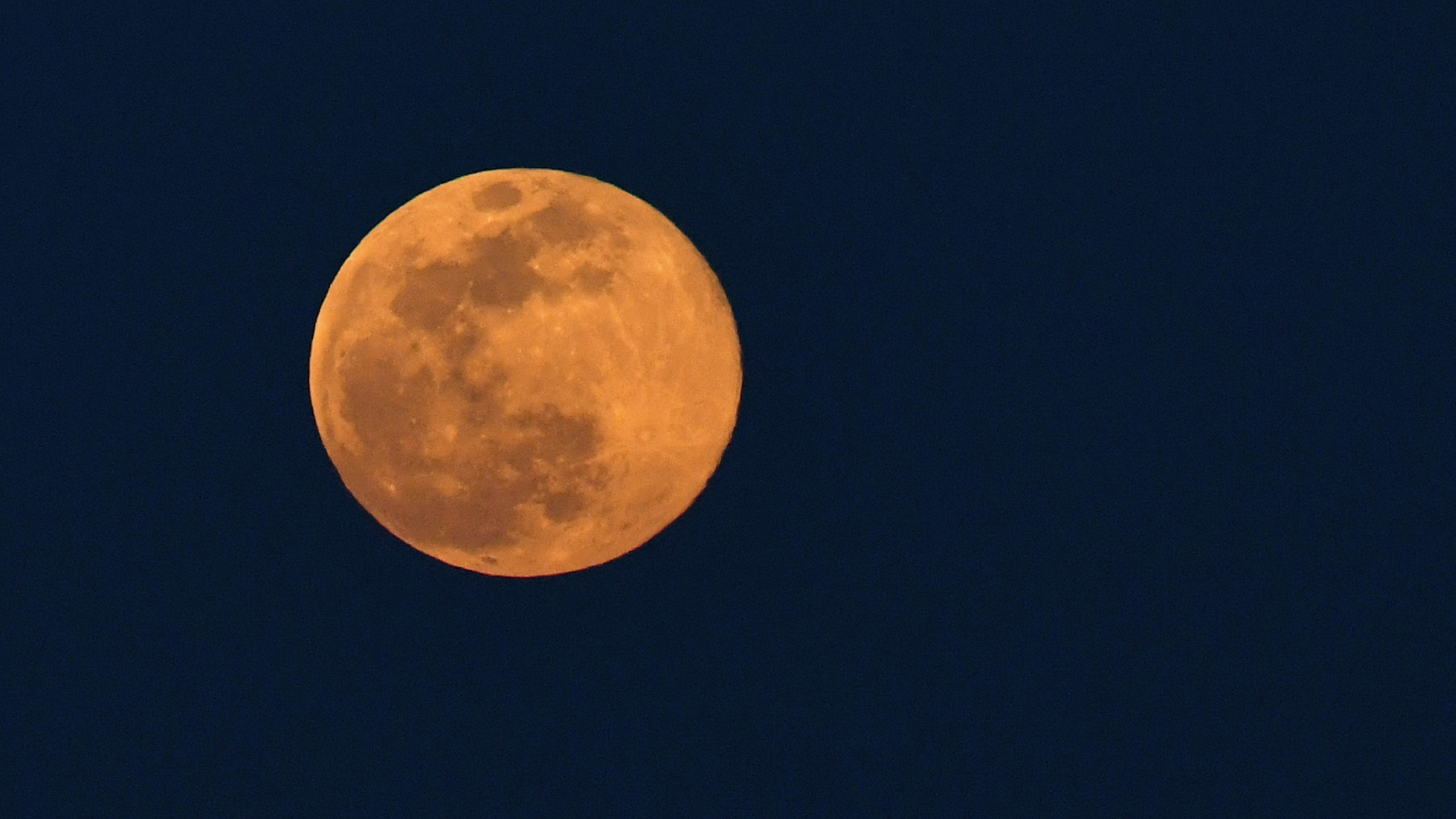 The super pink moon, the biggest supermoon of the year, is shown shortly after rising on April 7, 2020. in Las Vegas. The pink moon got its name because the April full moon occurs at the same time the pink wildflower Phlox subulata blooms in North America. A supermoon occurs when a full moon coincides with its perigee, which is its closest approach to the Earth. (Ethan Miller/Getty Images)