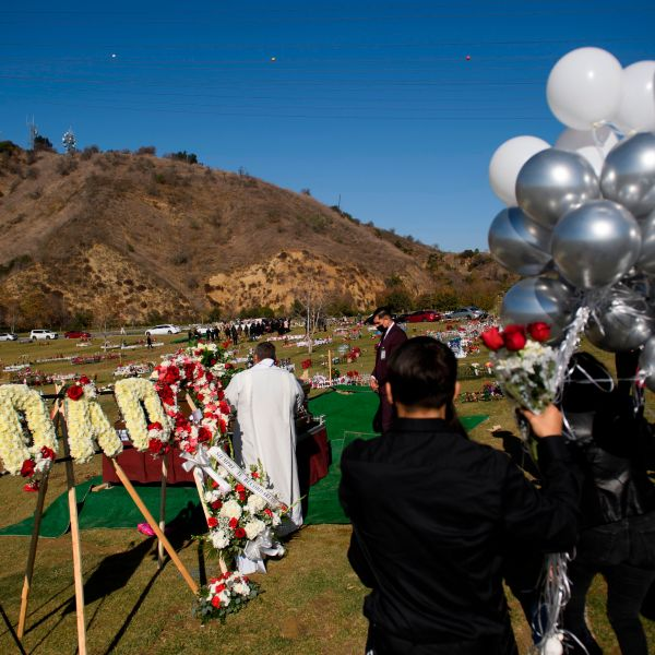Family members mourn during a burial service for Gilberto Arreguin Camacho, 58, following his death due to COVID-19, at a cemetery on New Year's Eve, December 31, 2020 in Whittier, California. (PATRICK T. FALLON/AFP via Getty Images)