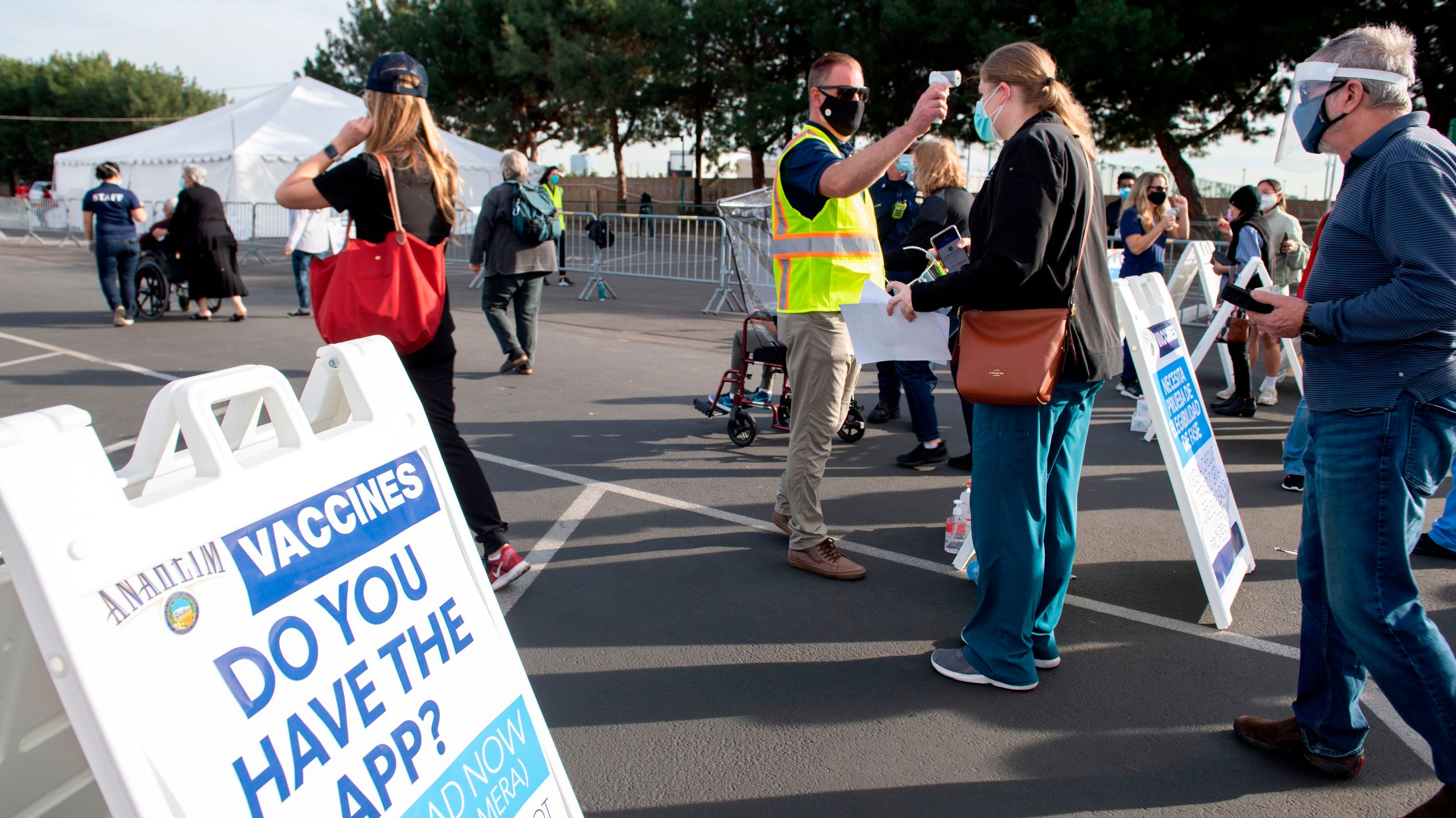 People have their temperature checked as they arrive at a Disneyland parking lot to receive COVID-19 vaccines on Jan. 13, 2021, in Anaheim. (VALERIE MACON/AFP via Getty Images)