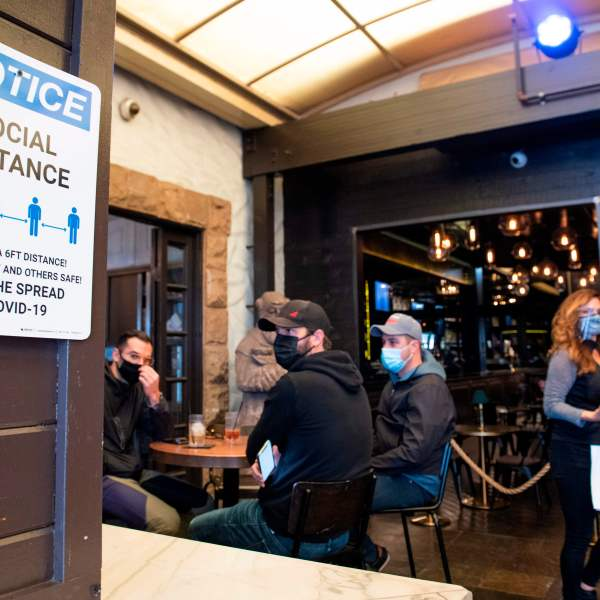 A notice inviting patrons to social distance is seen in the outdoor seating area of The Abbey Food & Bar on Jan. 29, 2021 in West Hollywood. (VALERIE MACON/AFP via Getty Images)