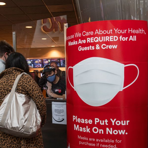 A sign asking people to wear a mask is displayed as moviegoers buy tickets at the AMC Burbank theatre on reopening day in Burbank on March 15, 2021. (VALERIE MACON/AFP via Getty Images)