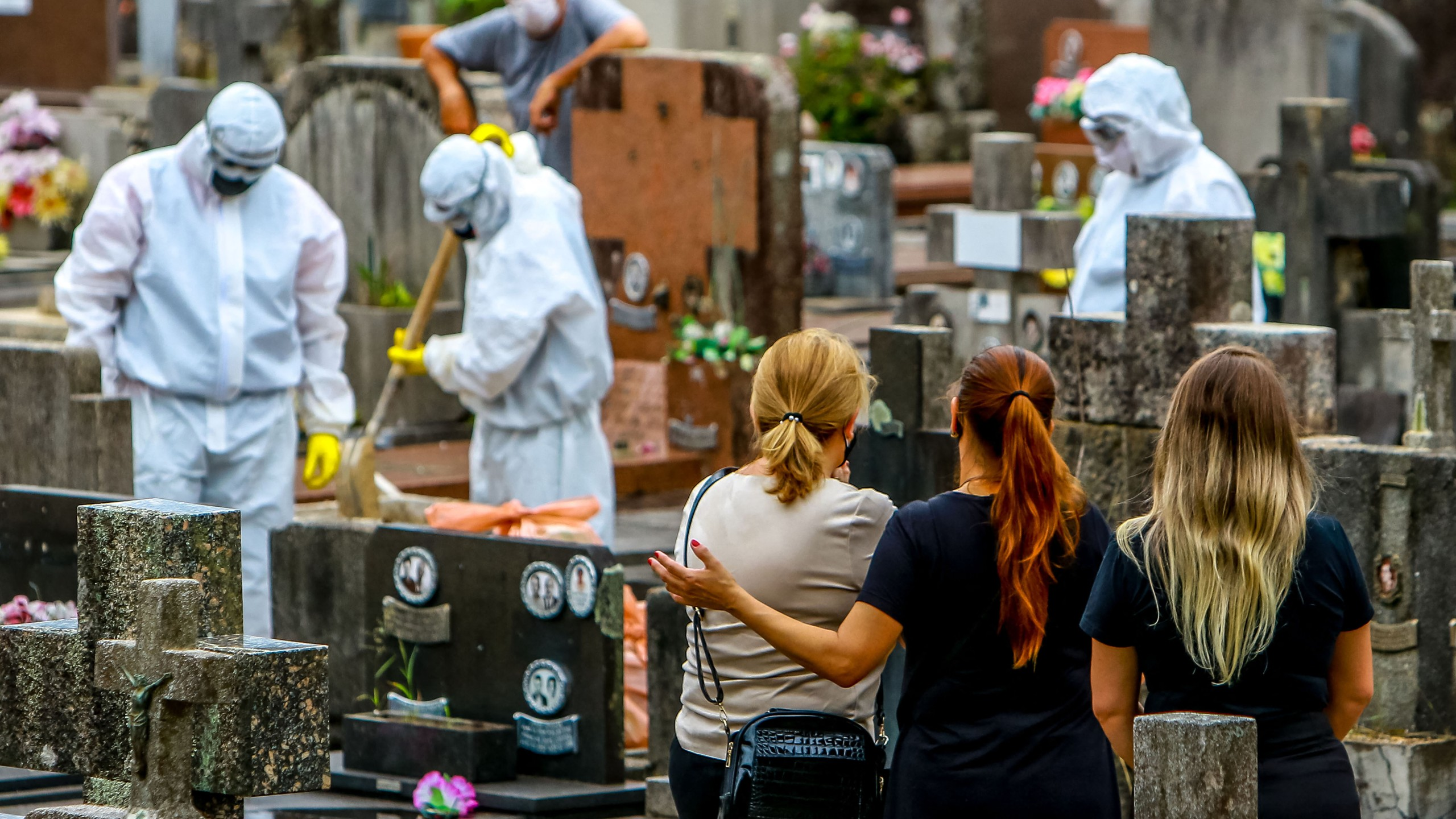 Relatives of a victim of COVID-19 watch as cemetery workers clean graves after a burial at the Sao Joao municipal cemetery in Porto Alegre, Brazil, on March 26, 2021. Brazil surpassed 100,000 new COVID-19 cases in one day that Thursday, adding another grim record in a country where the pandemic has killed more than 300,000 people. (SILVIO AVILA / AFP via Getty Images)
