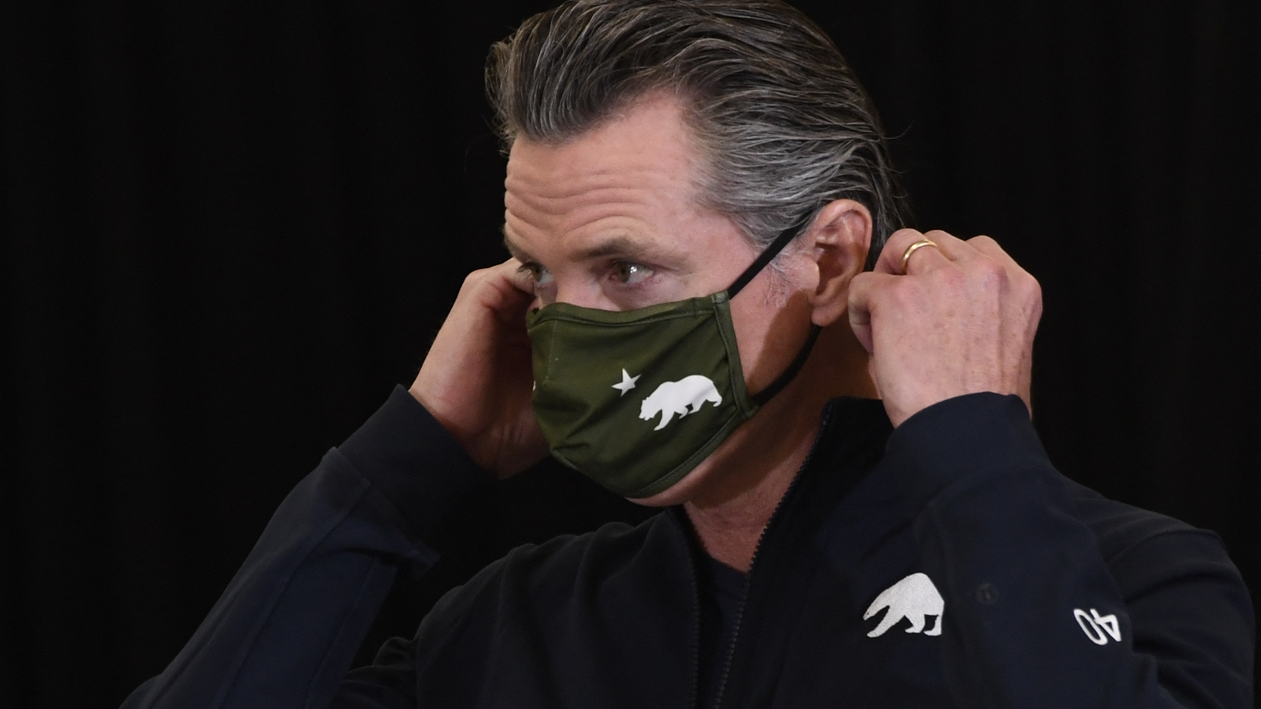 California Governor Gavin Newsom puts on his facemask after speaking to the media in Los Angeles on April 1, 2021. (PATRICK T. FALLON/AFP via Getty Images)