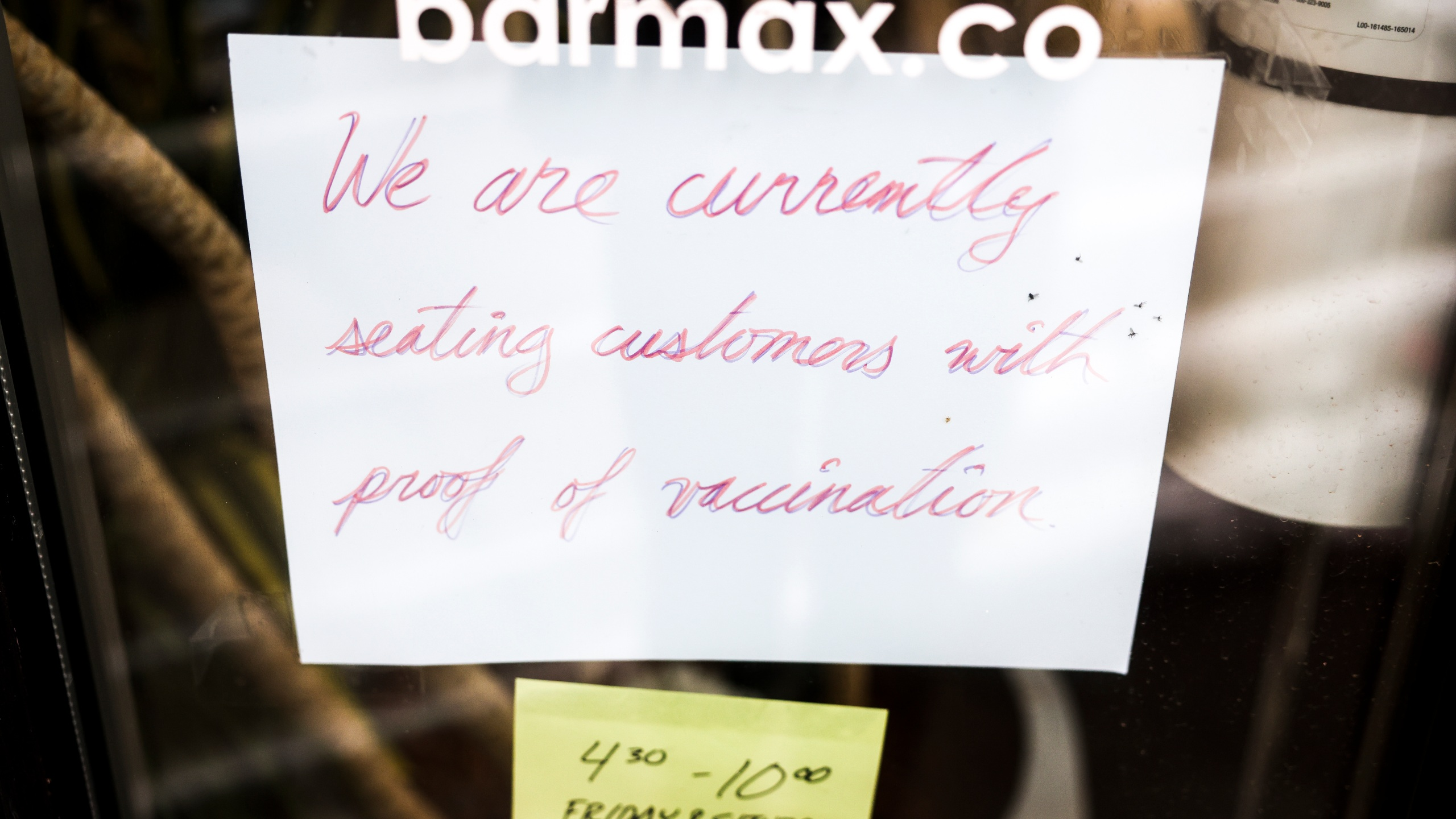 A sign in the window at Bar Max reads, We are currently seating customers with proof of vaccination, on April 16, 2021 in Denver, Colorado. (Photo by Michael Ciaglo/Getty Images)