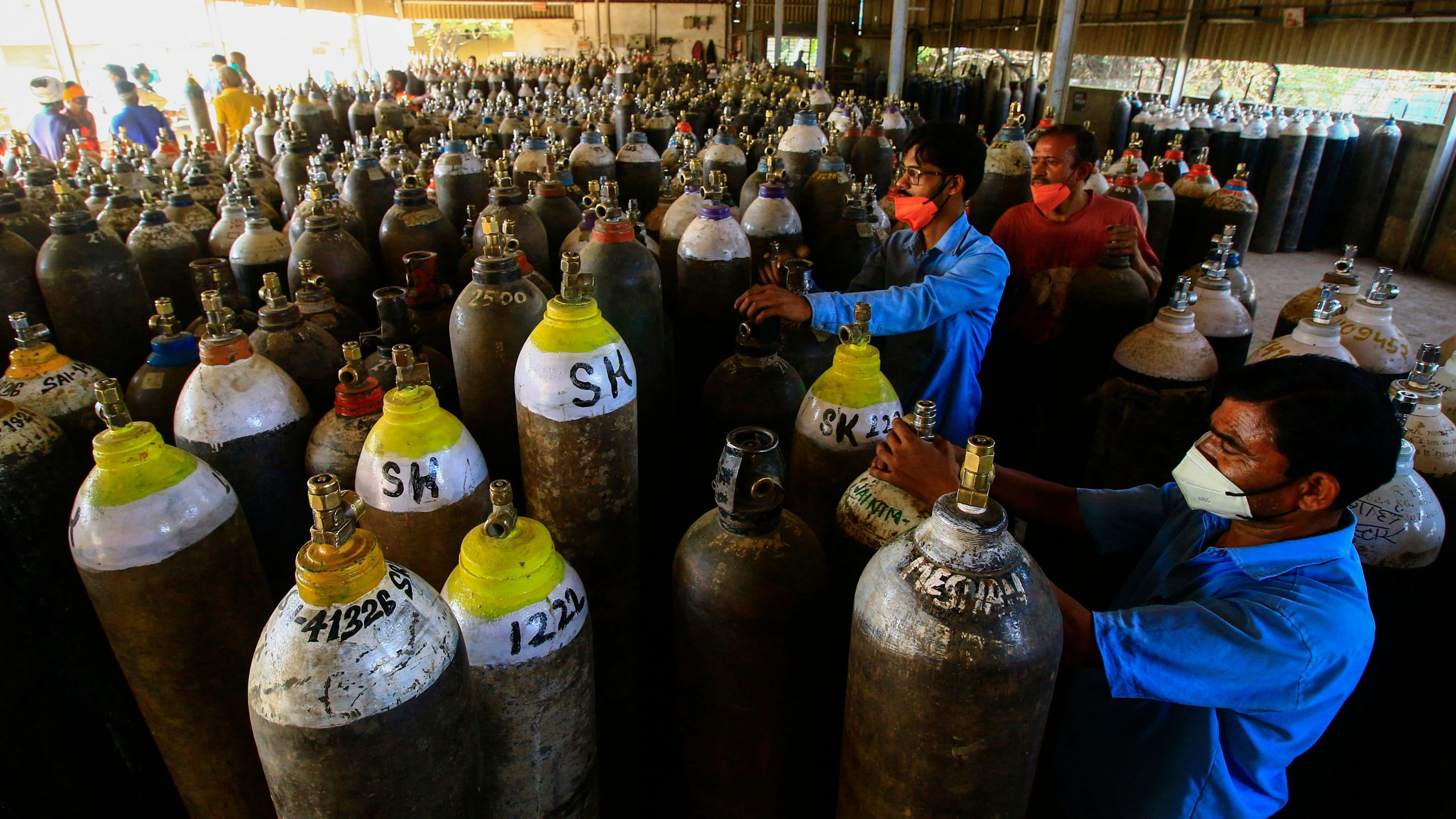 Workers prepare to fill medical oxygen cylinders for hospital use on COVID-19 patients on the outskirts of Jabalpur, India on April 18, 2021. (Uma Shankar/AFP via Getty Images)